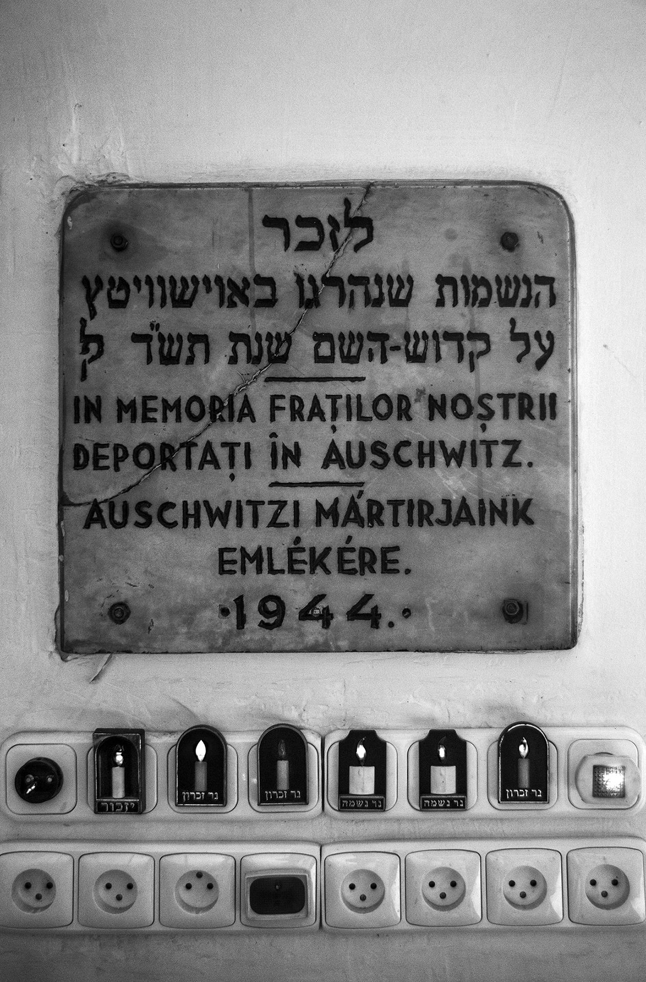 "A plaque hangs as a memorial above glowing electric candles at the Sas Chevra Synagogue in Oradea on August 28, 2013. The plaque reads, ""In memory of our brothers and sisters deported to Auschwitz."" (Photo by Daniel Owen/GroundTruth)"