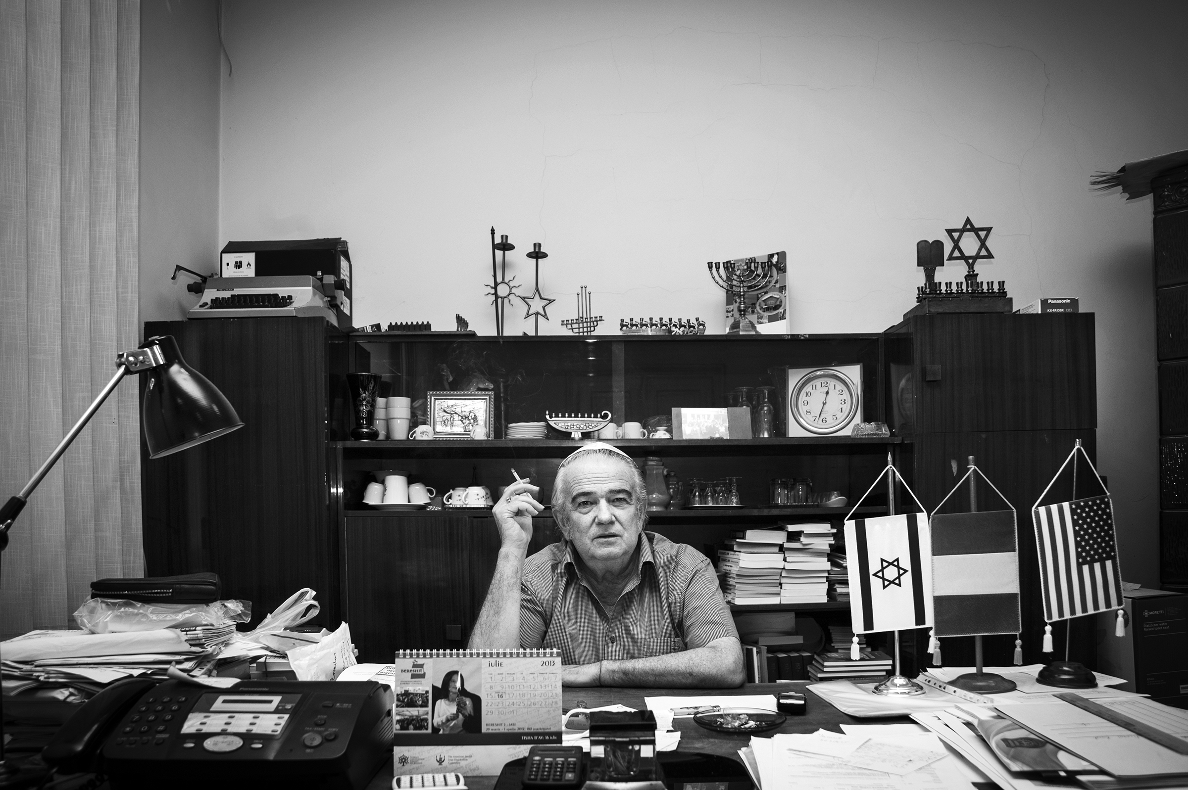Teodor Koppelmann, President of the Jewish Community Center in Oradea, Romania, sits behind his cluttered desk where he often chains-mokes while overseeing the day-to-day business and attending to the needs of his community members on August 26, 2013. (Photo by Daniel Owen/GroundTruth)