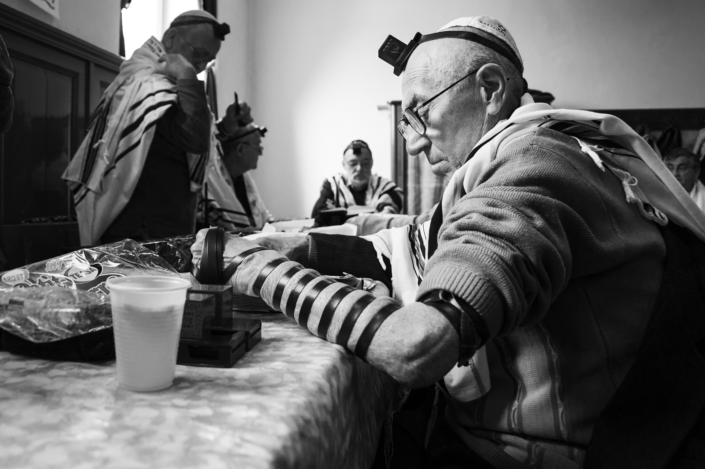 Zakaria Salman studies a religious text with the other members of the minyan in Oradea's only remaining active Sas Chevra Synagogue on April 11, 2013. (Photo by Daniel Owen/GroundTruth)