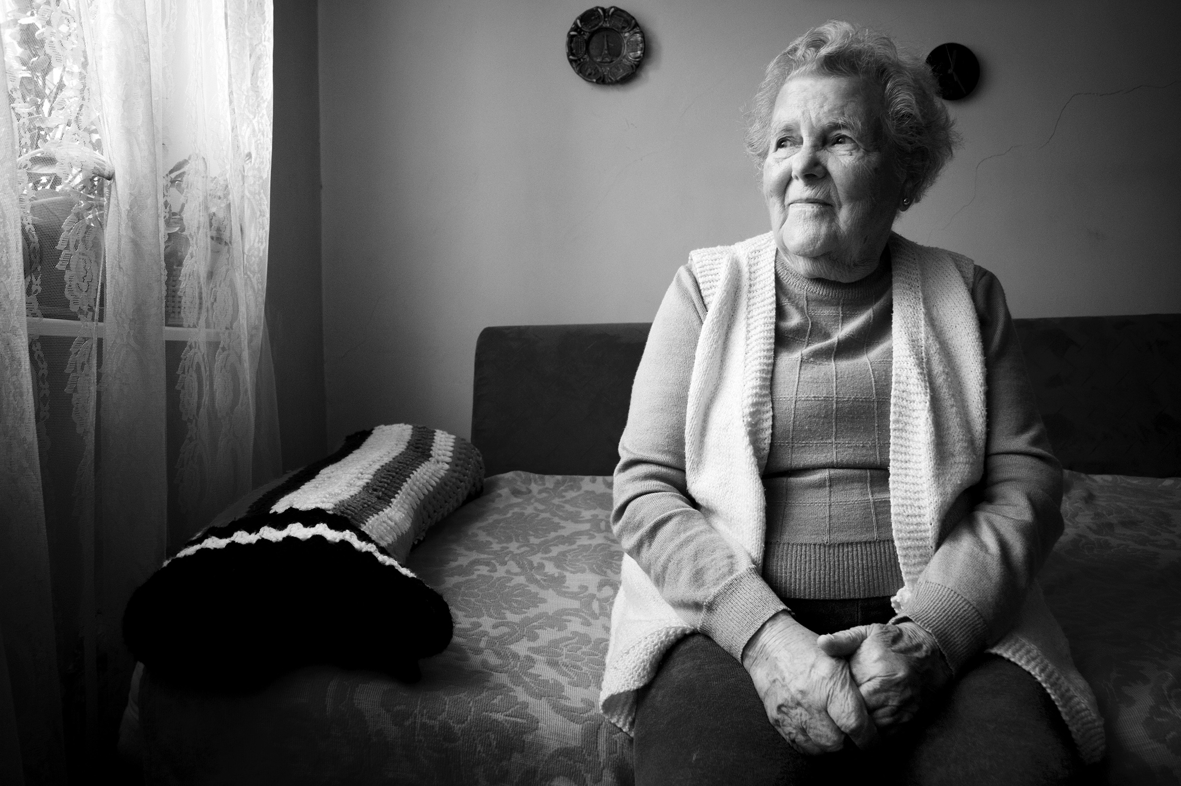 Vioara 'Ibby' Braun (Rosenzweig), 87, poses for a portrait in her home in Oradea, Romania on January 9, 2015. Born in Marghita, Romania, a town under Hungarian control during the war, Braun was deported at the age of seventeen to the Bergen Belsen concentration camp. She survived to be married her late husband, Tiberiu, an Auschwitz survivor. After the war, Braun would spend five years working for the Women's Anti-Fascist Union in Romania, and later as a secretary for the Women's Democratic Union. (Photo by Daniel Owen/GroundTruth)