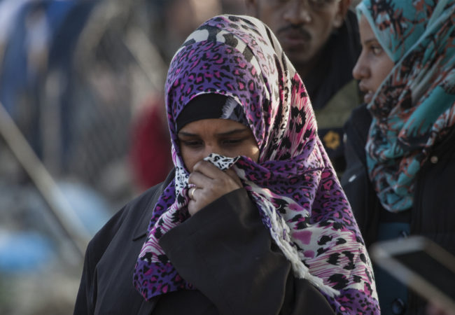 A woman stands and covers her face in Greece among a crowd of other refugees. (Photo by Steve Evans/Flickr Creative Commons)