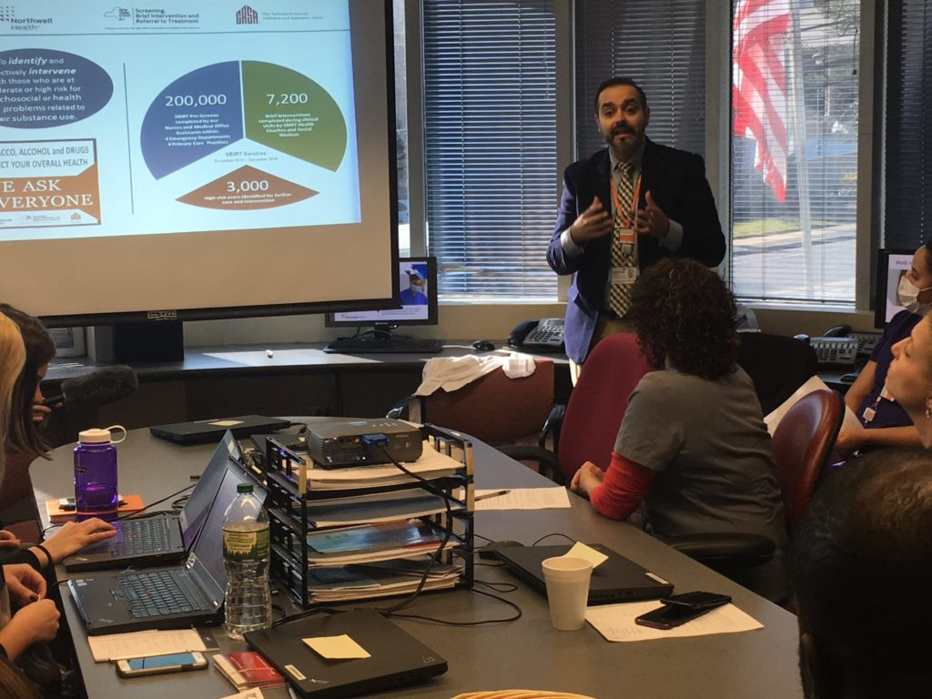 Dr. Sandeep Kapoor leads an SBIRT training seminar at the Division of Internal Medicine, one of Northwell's pilot sites for the substance use screening process. SBIRT stands for Screening, Brief Intervention, and Referral to Treatment. (Photo by Joaquin Cotler/GroundTruth)