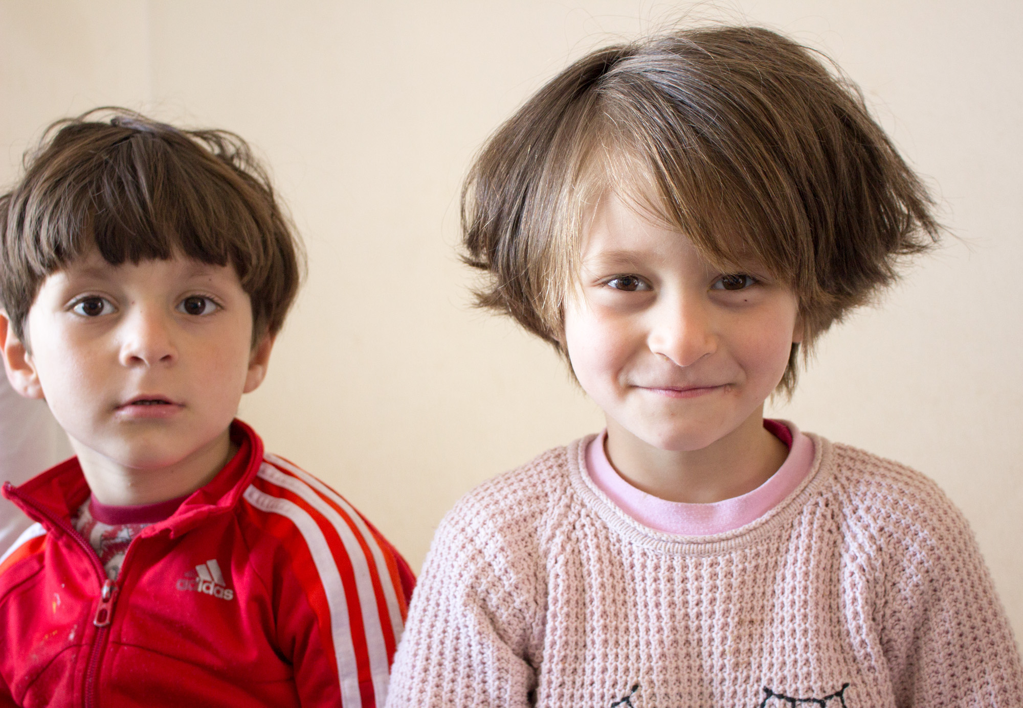 After running around outside, two of Alia Habesh's children sit on a twin bed in their cramped, but tidy apartment in Sindos. They're both recovering from tuberculosis, contracted while fleeing Aleppo, and enjoy playing with any visitors. (Photo by Catherine Clark/GroundTruth)