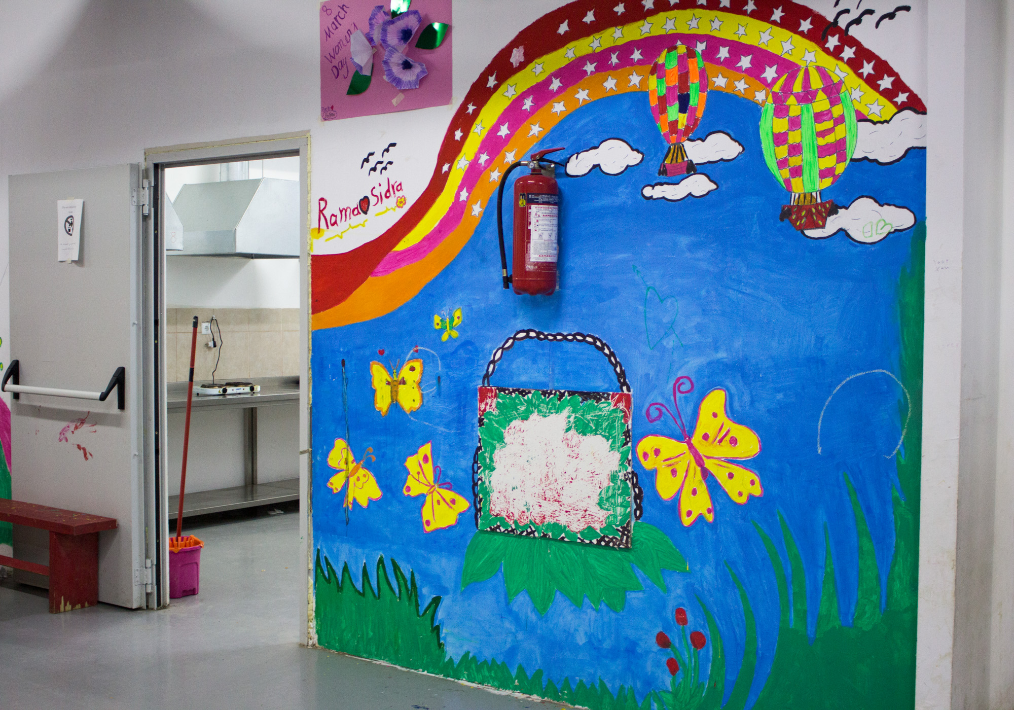 Throughout Elpida Home, murals line the walls. The communal kitchen is around the corner of this fluorescent mural. Residents can make their own meals and chat through the window that peers out into the tea room. (Photo by Catherine Clark/GroundTruth)