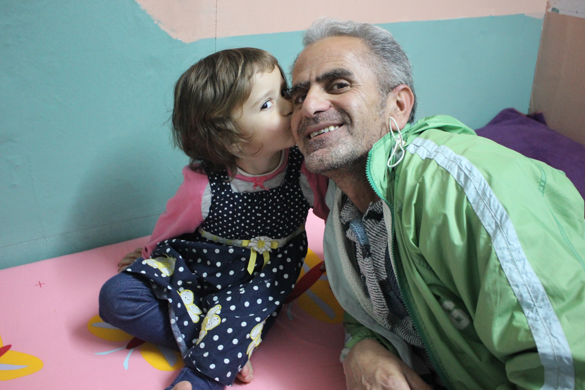 A young Syrian girl kisses her father's cheek inside their colorfully decorated room at Oinofyta, a refugee site outside of Athens, Greece. (Photo by Alexandra Meeks/GroundTruth)