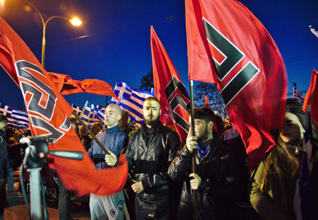 Golden Dawn members hold their party's flags during a March 2015 rally in Athens, Greece. (Photo via Wikimedia Commons)