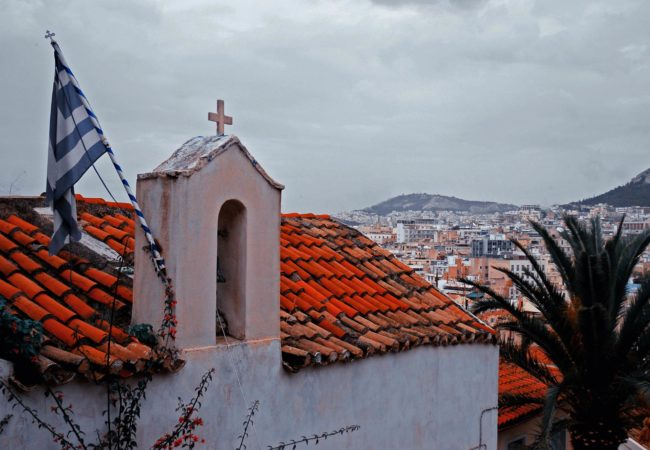A Greek flag hangs from the roof of a small church overlooking Athens. (Photo by Mstyslav Chernov/Wikimedia Commons)