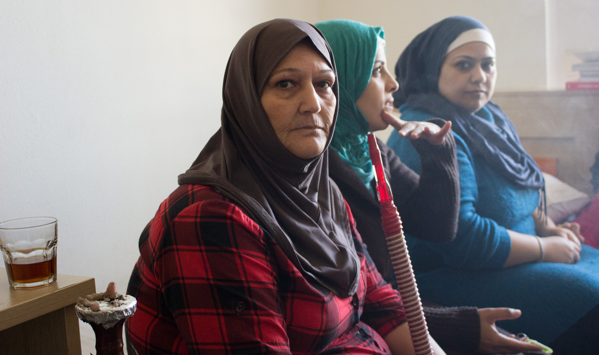 Grasping a hookah pipe, Syrian refugee Hanifa Hussein sits on a twin bed with her older daughter (right) and family friend (left). Smoking is a common way adult residents pass time at the Sindos apartment complex outside Thessaloniki, Greece (Photo by Catherine Clark/GroundTruth)
