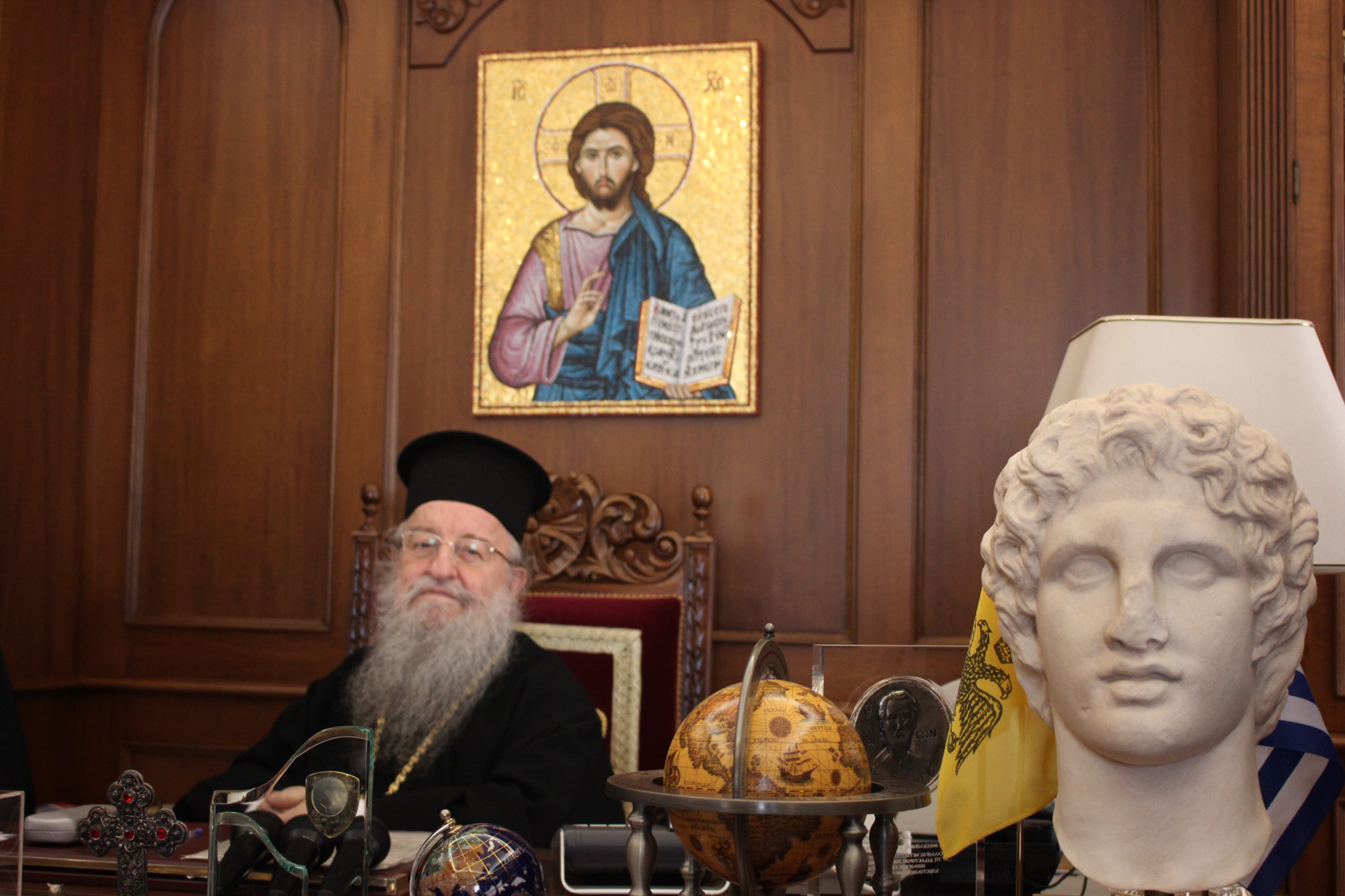 Bishop Anthimos of Thessaloniki sits behind his desk in the city's cathedral. The Greek Orthodox Church has come under fire from NGOs and volunteers for not doing more for refugees in Greece. (Photo by Alexandra Meeks/GroundTruth)