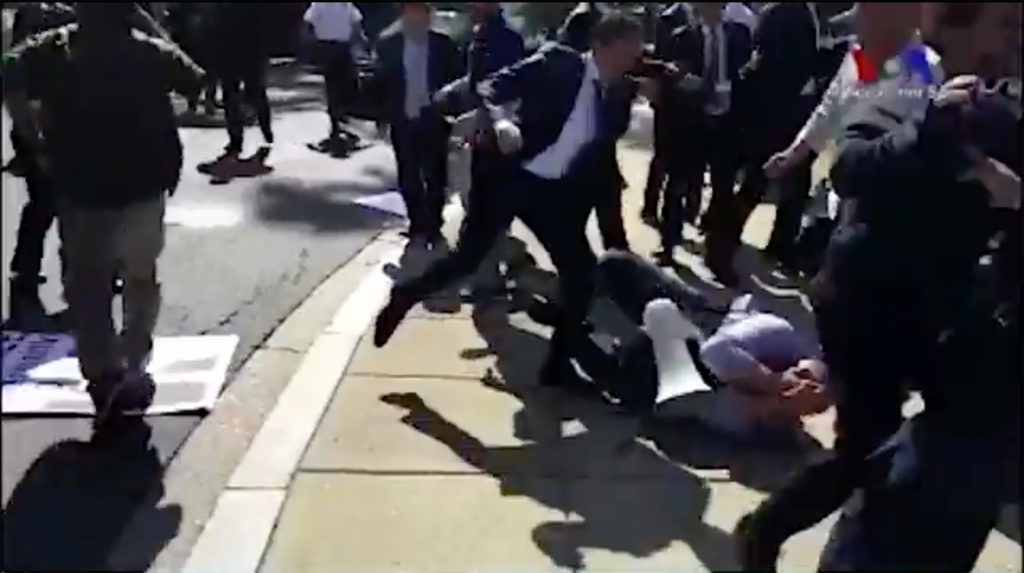 In this screenshot from a video posted on Twitter by VOA Turkish, a man can be seen kicking a protester on the ground.