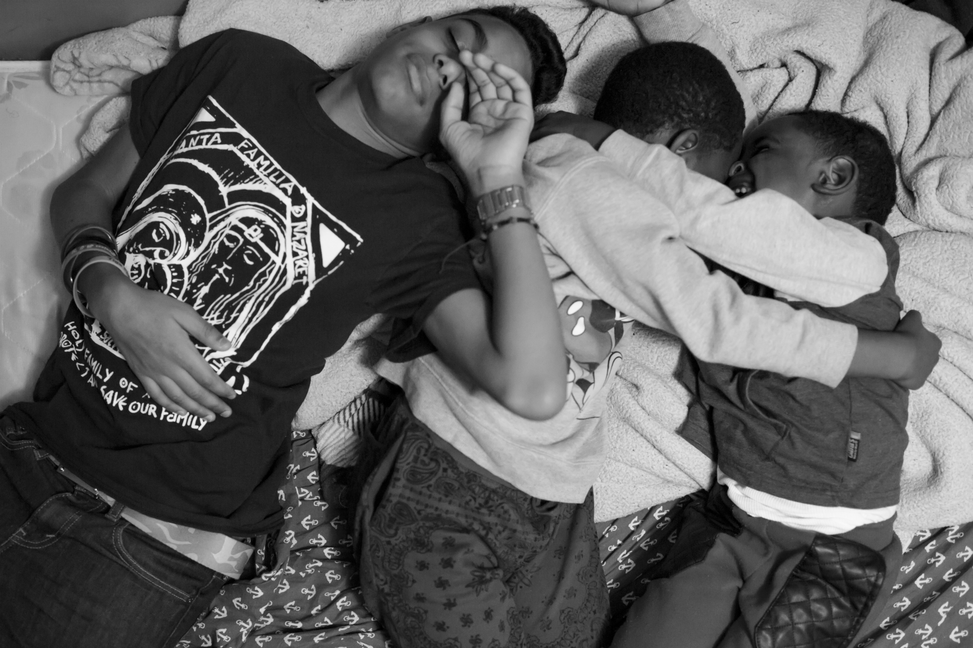 Chavi Leon rests with his two cousins, Jeremy and Jerry Mateo, at their relatives', the Demoyas, house in the Bronx on Feb. 6, 2016, New York City. The Leons are from the Dominican Republic, but keep strong family connections in New York. (Photo by Sarah Blesener/GroundTruth/Alexia Foundation)