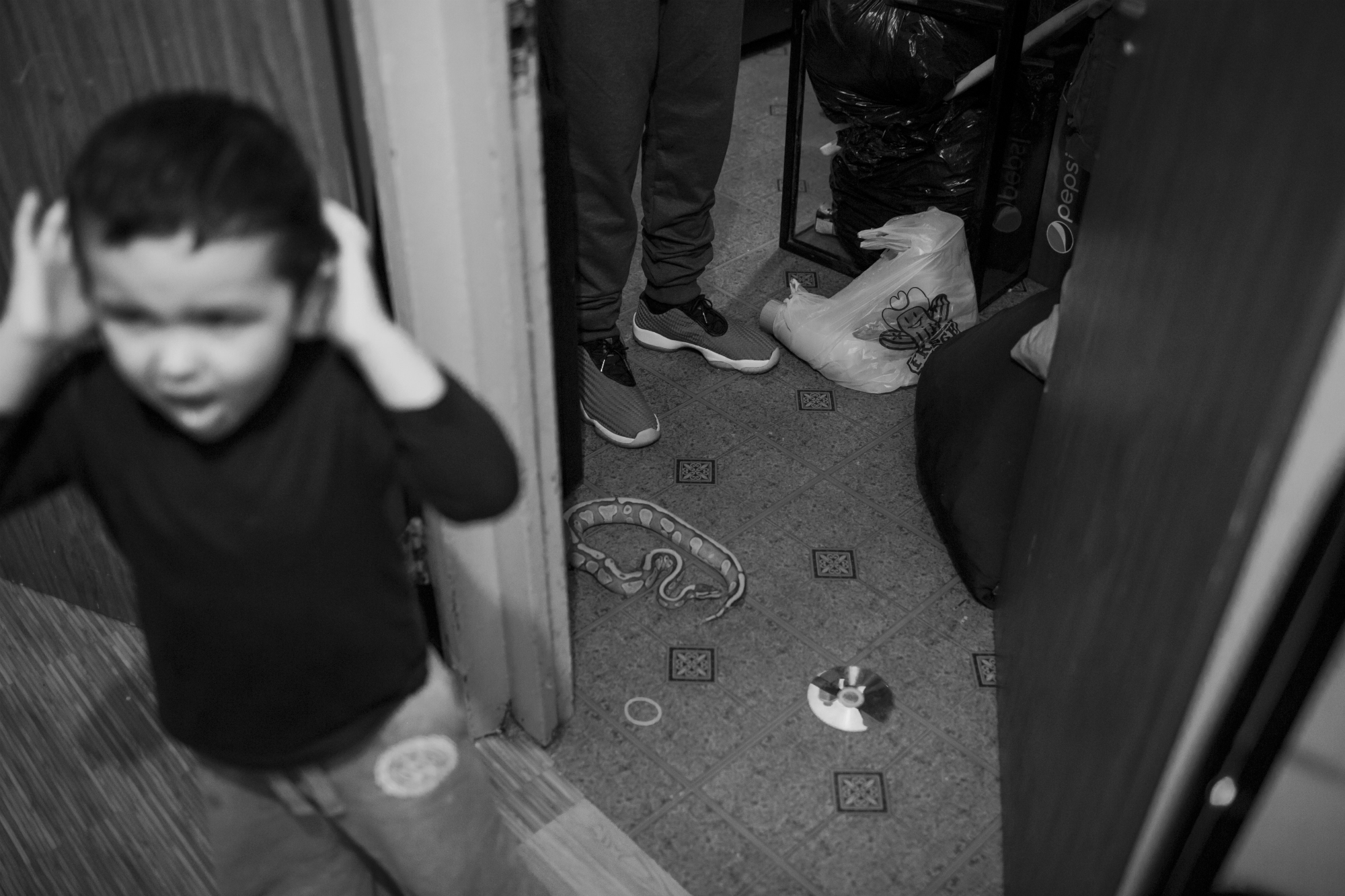 Two-year-old Christopher Oritz calls for his mother across the hallway in the Neiras' apartment, April 13, 2016, Mott Haven Houses, Mott Haven, New York. Christopher is autistic, and lives with his mom, grandma, and uncles at the Neiras' apartment. (Photo by Sarah Blesener/GroundTruth/Alexia Foundation)