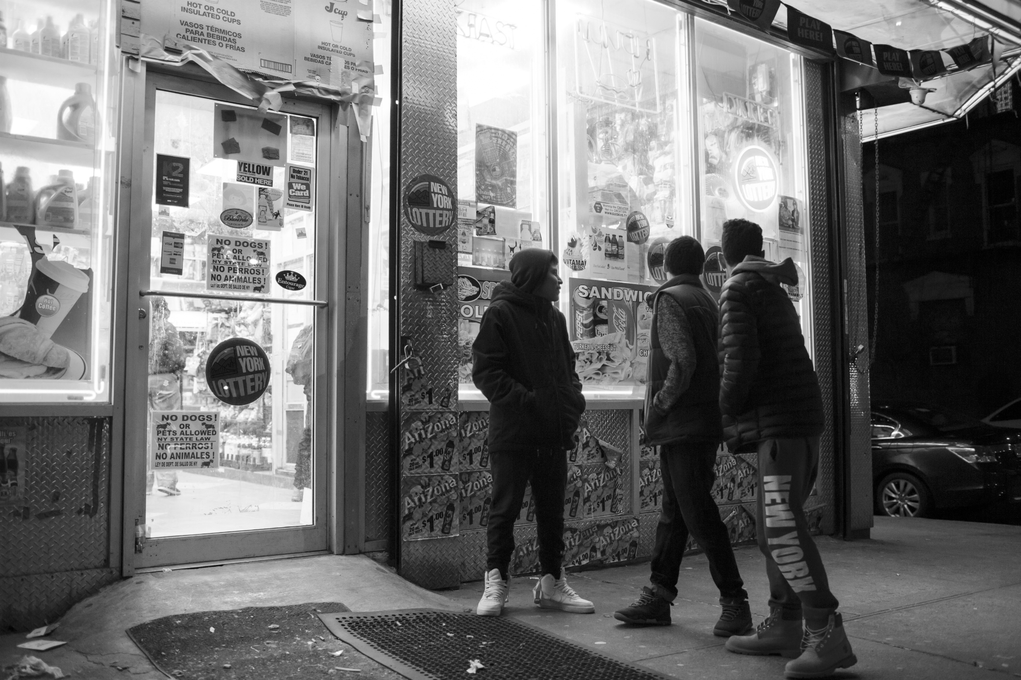 Marco Vasquez, Edwin Amaro, and Chavier Leon watch as a drunk man yells at a woman around the corner. February 26, 2016, Mott Haven, South Bronx, New York City. (Photo by Sarah Blesener/GroundTruth/Alexia Foundation)