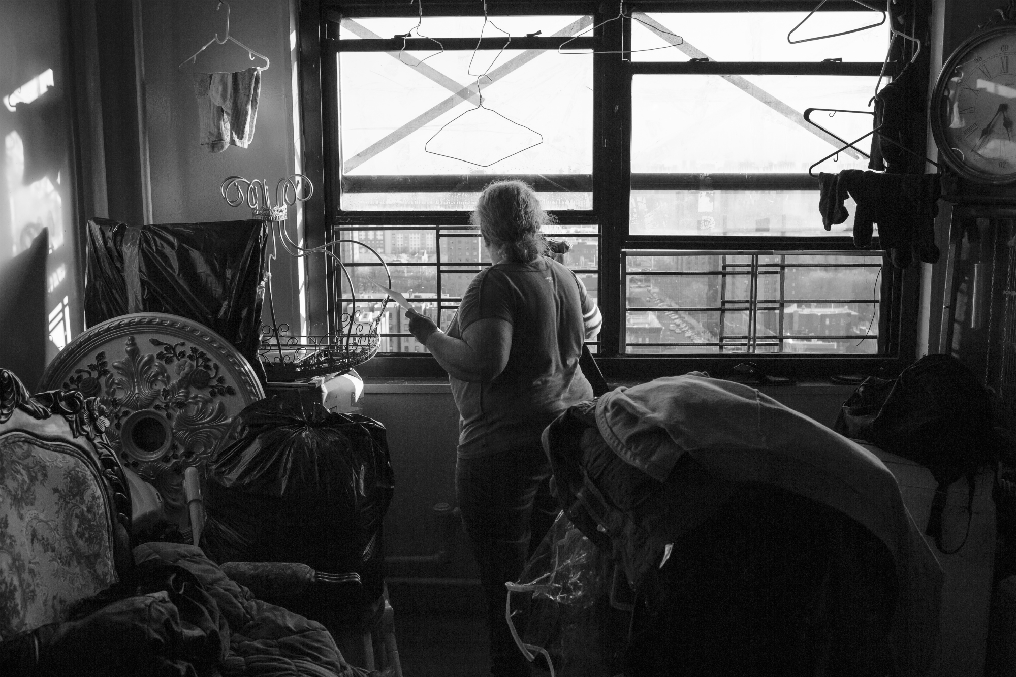 Juan Neira's mother inside the living room of their apartment, April 13, 2016, Mott Haven, South Bronx. (Photo by Sarah Blesener/GroundTruth/Alexia Foundation)