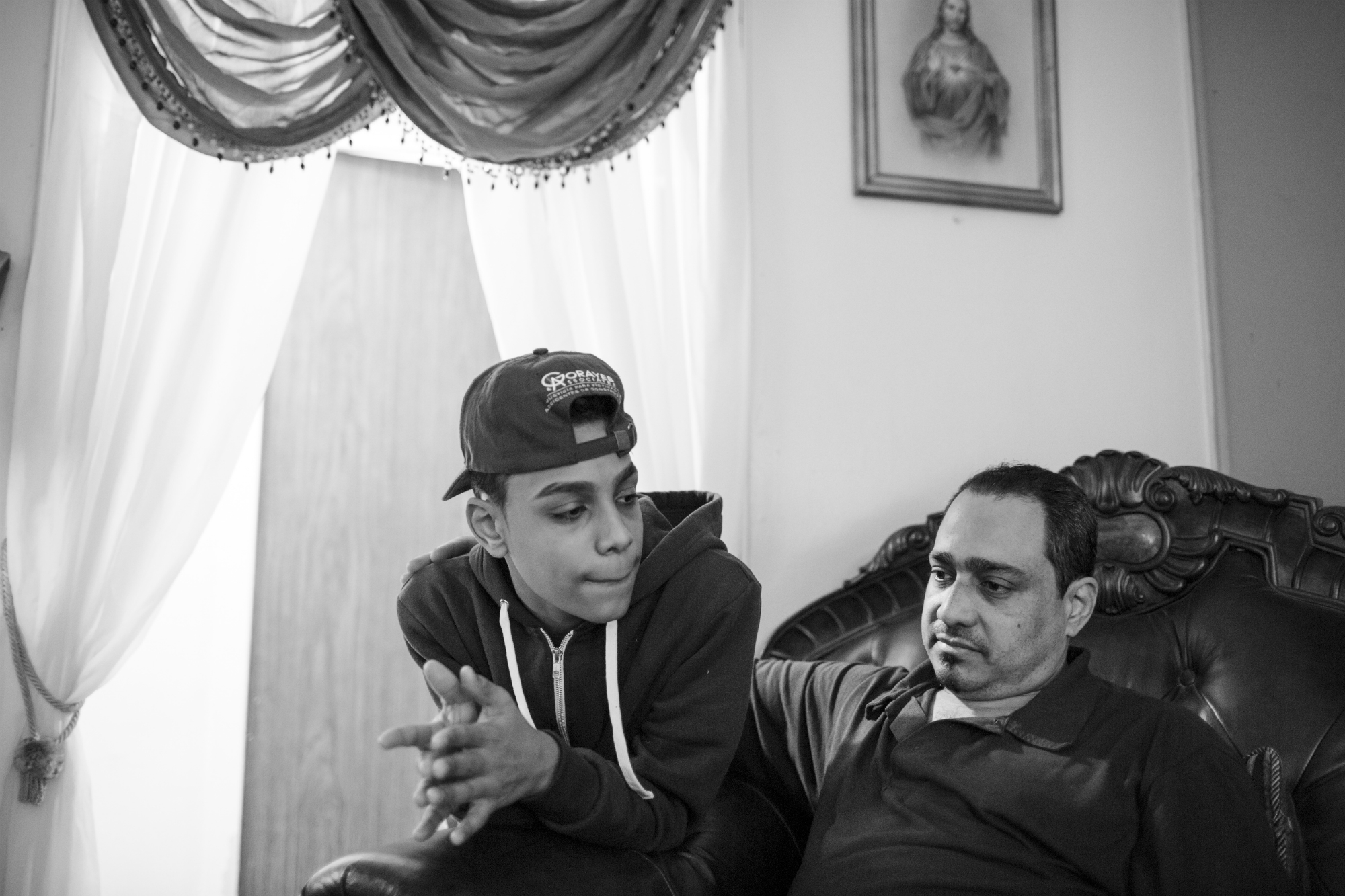 Chavi Leon with his dad in their living room, Feb 27, 2016, Patterson Projets, Mott Haven, South Bronx. Chavi's dad is one of his greatest inspirations in his life, pushing him to finish high school and pursue music. (Photo by Sarah Blesener/GroundTruth/Alexia Foundation)