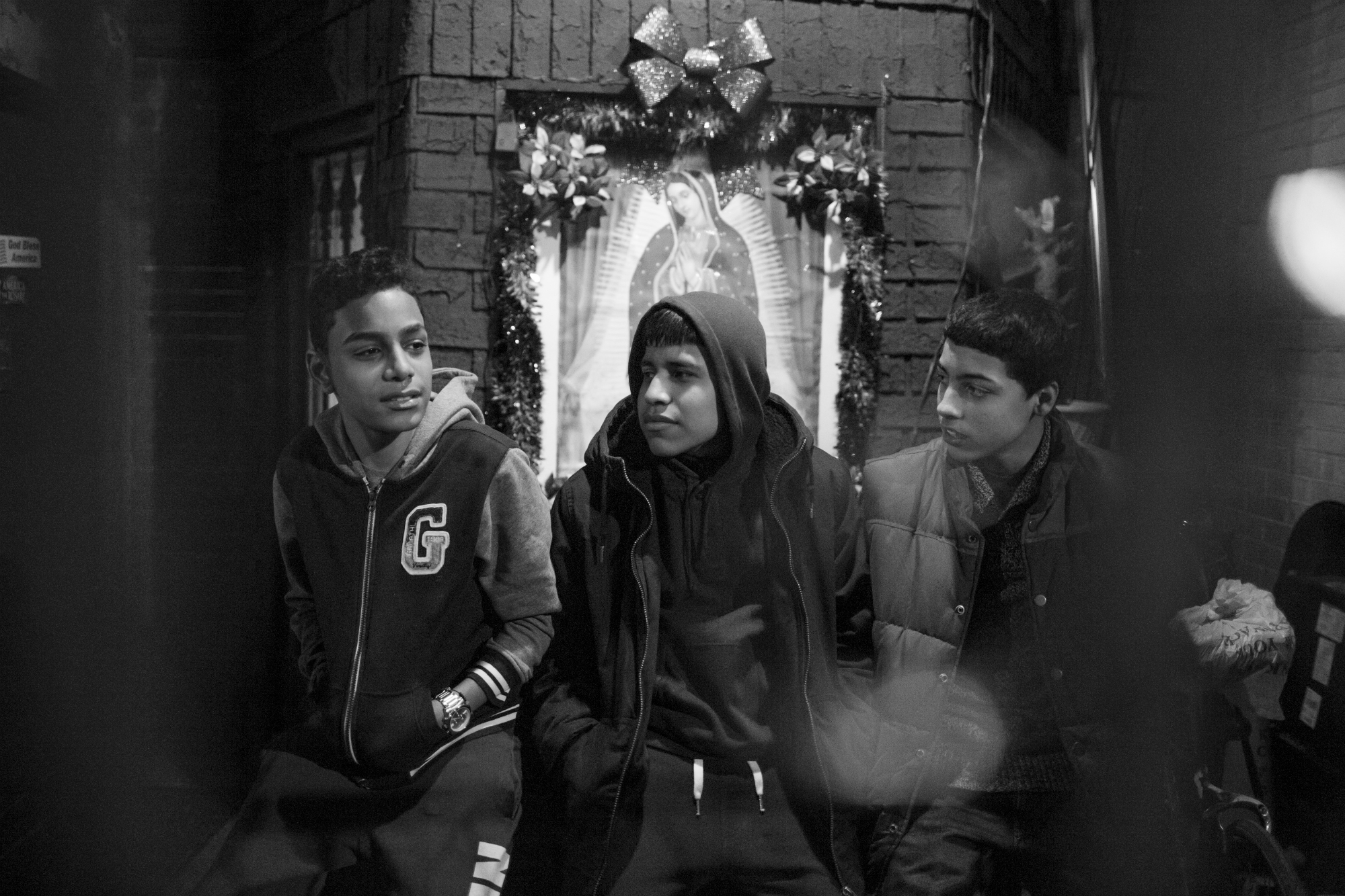 Chavi Leon, Marco Vasquez and Edwin Amaro sit outside of Marco's apartment in Mott Haven, February 26, 2016, South Bronx, New York. (Photo by Sarah Blesener/GroundTruth/Alexia Foundation)