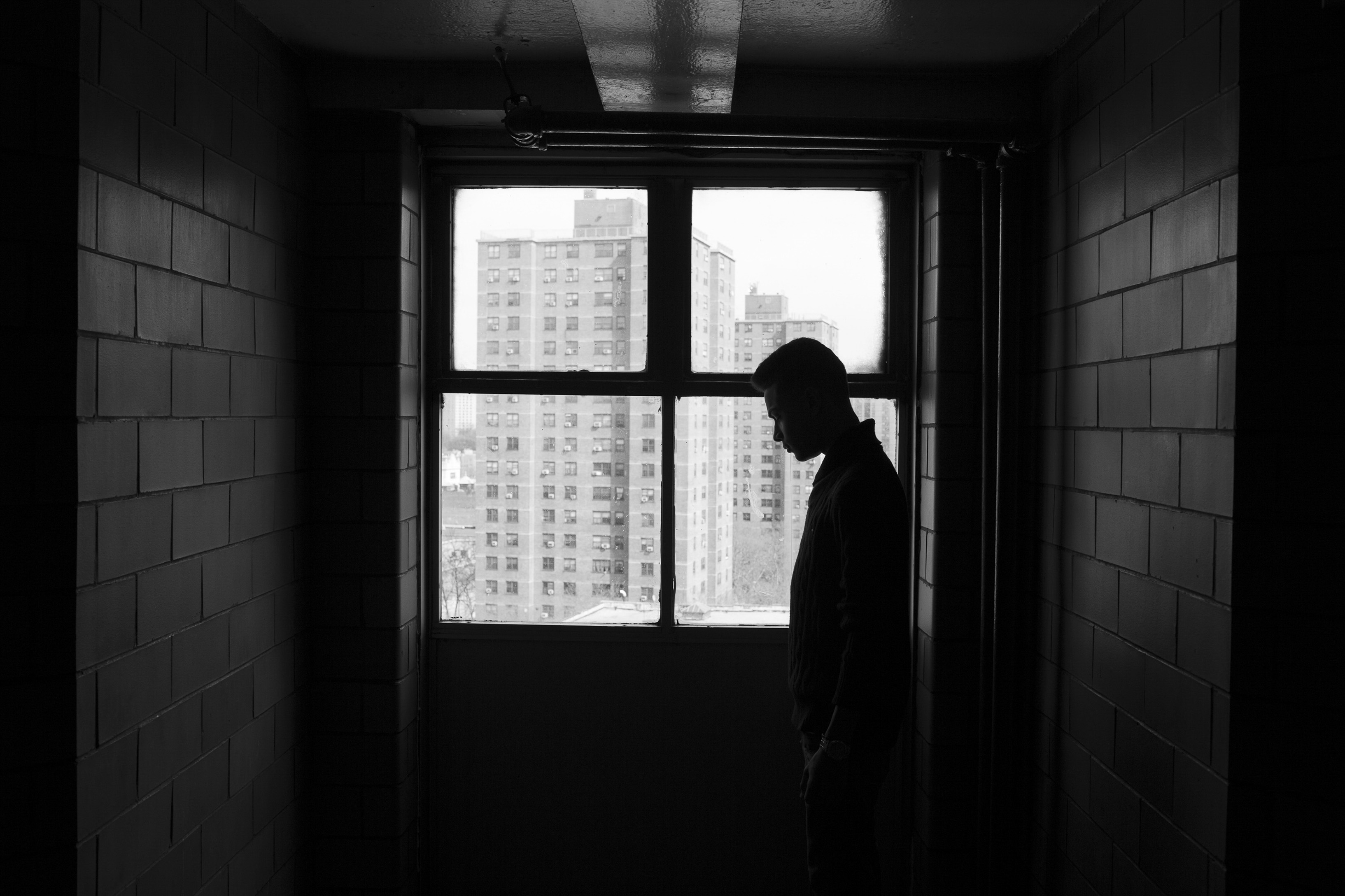 Chavi Leon stands in the hallway of his family's apartment during spring break on April 17, 2016, Mott Haven, South Bronx, New York. (Photo by Sarah Blesener/GroundTruth/Alexia Foundation)