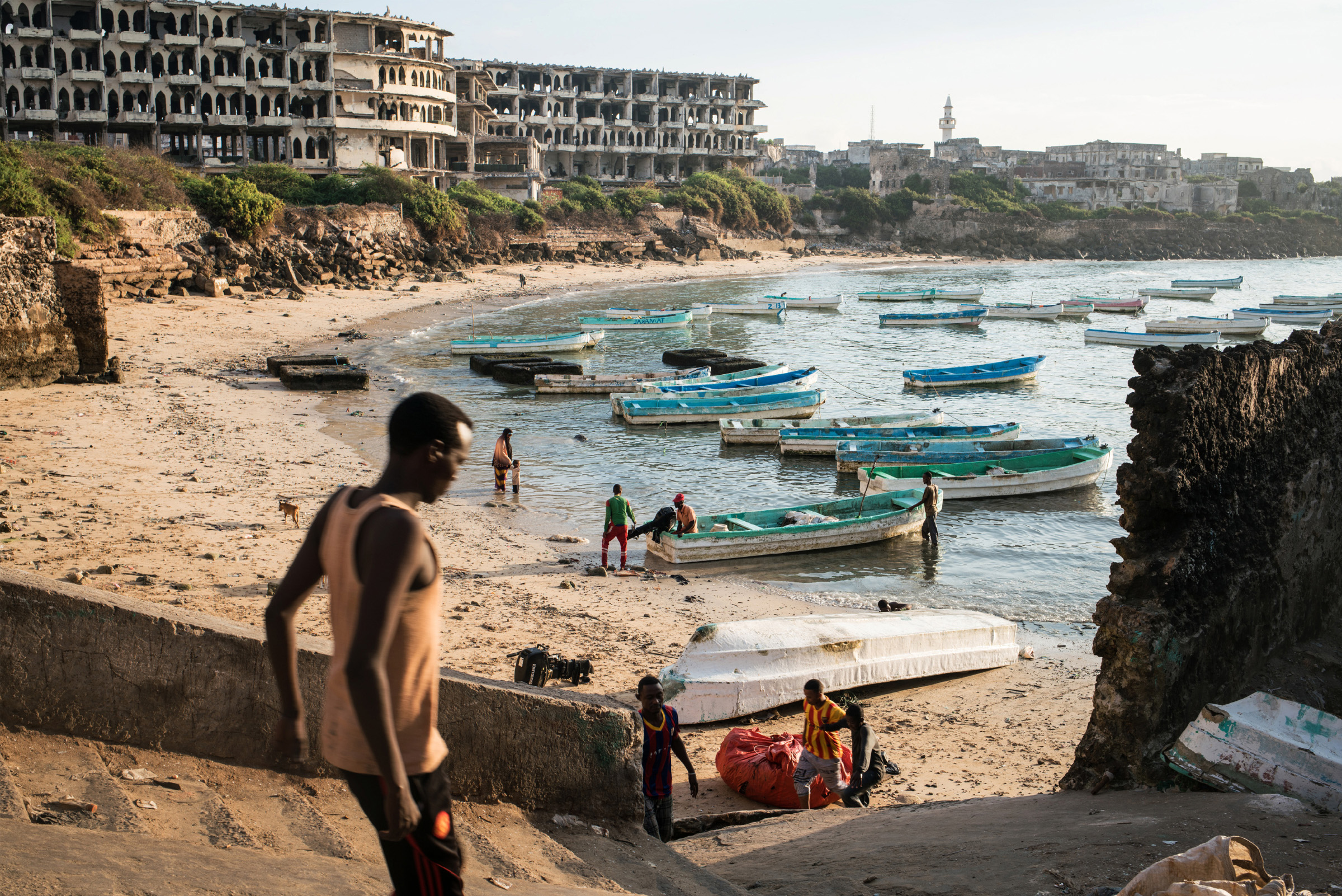 Boats gather at dawn in the old port in Mogadishu, the Somali capital, as fishermen land their catch and ready it for transport to the city's fish market. (Photo by Nichole Sobecki/GroundTruth)