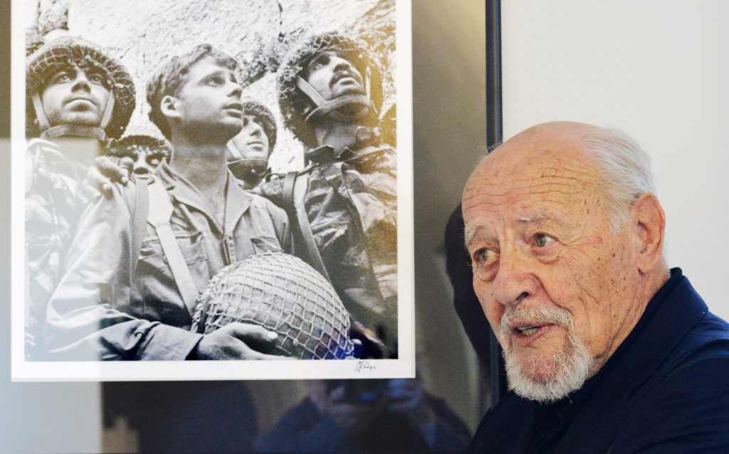 """Israeli photographer David Rubinger poses with his famous photo of three Israeli paratroopers after the recapture the Western Wall in the Six-Day War at an exhibition called """"Israel Through My Lens"""" in Old Town Hall, Prague, Czech Republic, on July 3, 2014. (CTK Photo/Michal Dolezal)"""