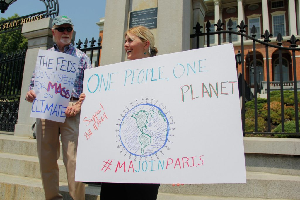 Rob Stenson, left, and Jessica Lambert show their support for the Paris Agreement outside the Massachusetts State House. Massachusetts has joined a coalition of states, known as the U.S. Climate Alliance, that have pledged to maintain the climate goals of the Paris Agreement. Additionally, the Massachusetts legislature is considering adopting a bill to make the climate goals a state law. (Photo by Ellen Kanzinger/GroundTruth)