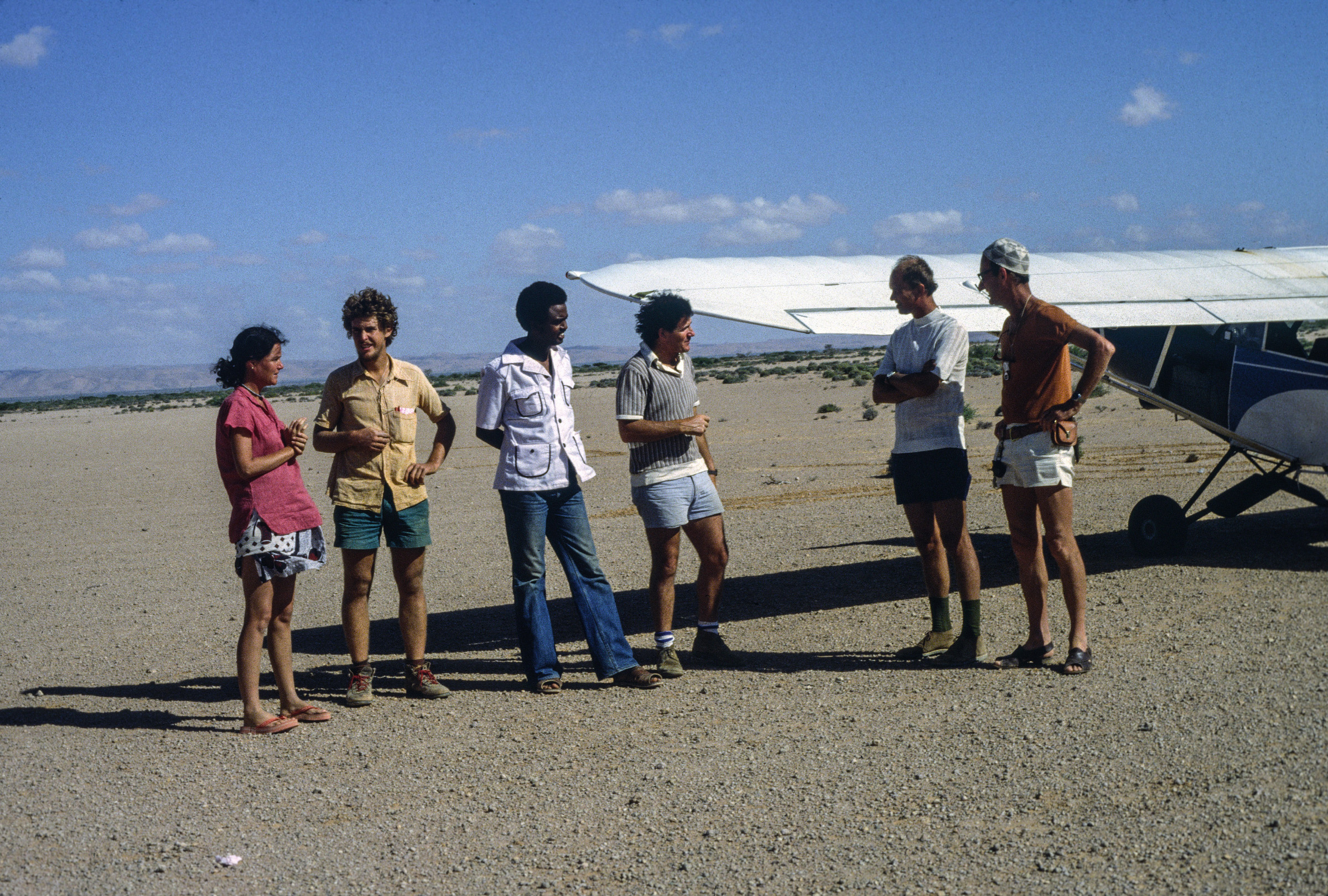 Watson and his researchers stand on a tarmac in Somalia. Archival Photo.
