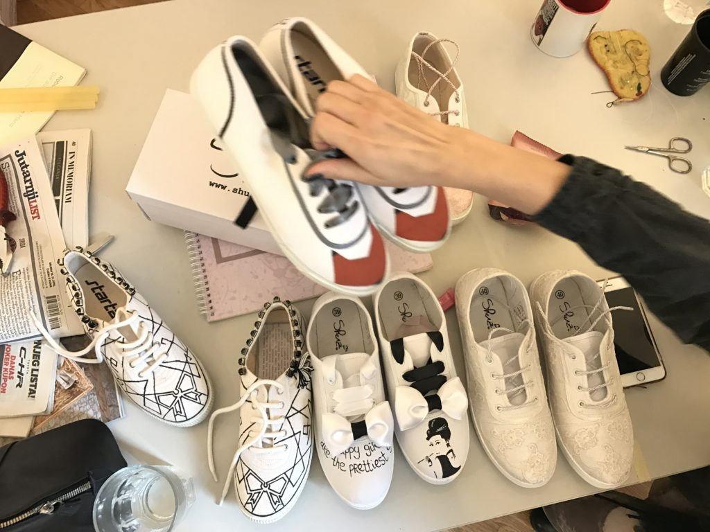 Maja Žirovčić rearranges the hand-painted shoes she's designed with co-founder, Ljudmila Mihajlović. (Photo Credit: Kristina Chorvath)