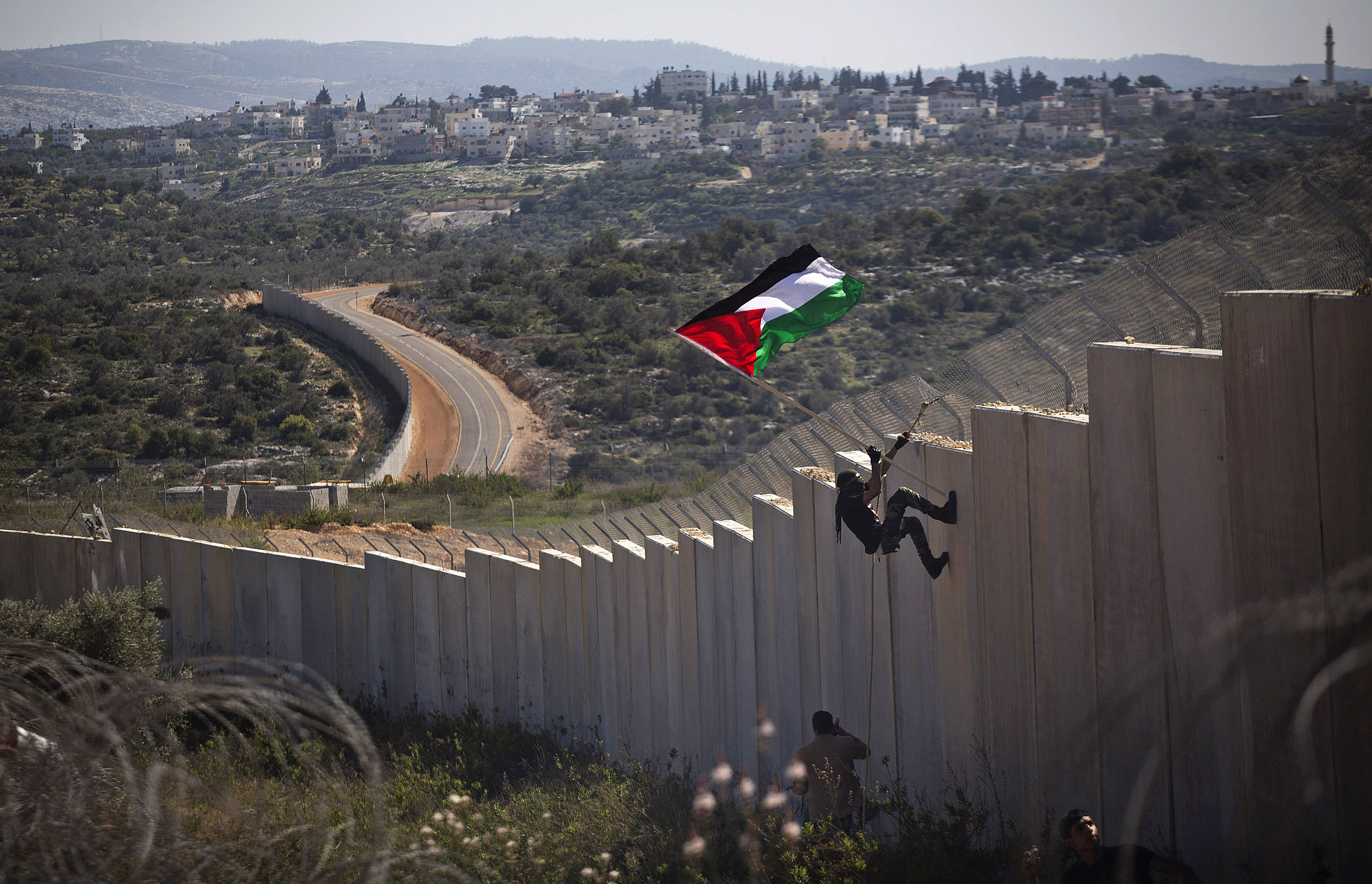A Palestinian youth placed a flag on the Israeli Separation Wall during a protest marking nine years for the struggle against the wall in the West Bank village of Bil'in, February 28, 2014. (Photo by Oren Ziv/GroundTruth)