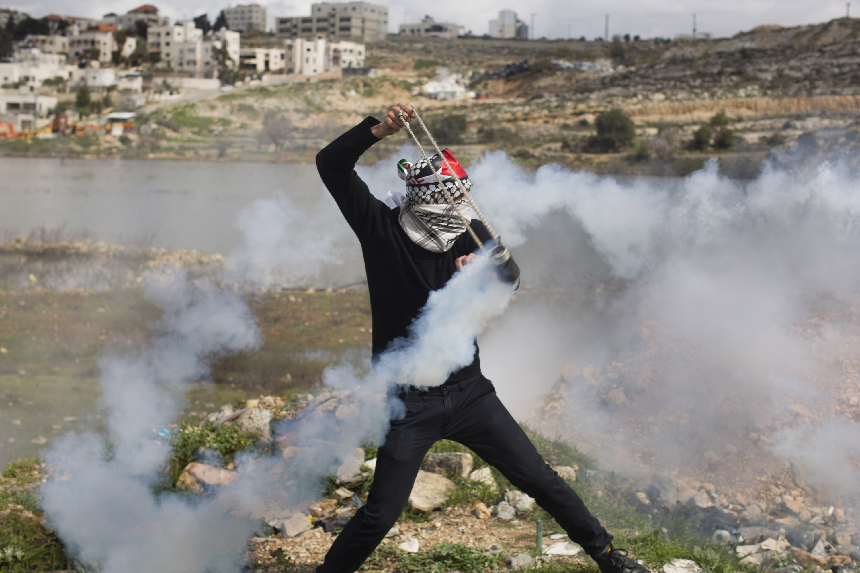 A Palestinian youth used his sling shot to throw back a tear gas canister fired by the Israeli army during a solidarity protest for prisoners, at Ofer military prison in Bituniya, West Bank, February 19, 2013. (Photo by Oren Ziv/GroundTruth)