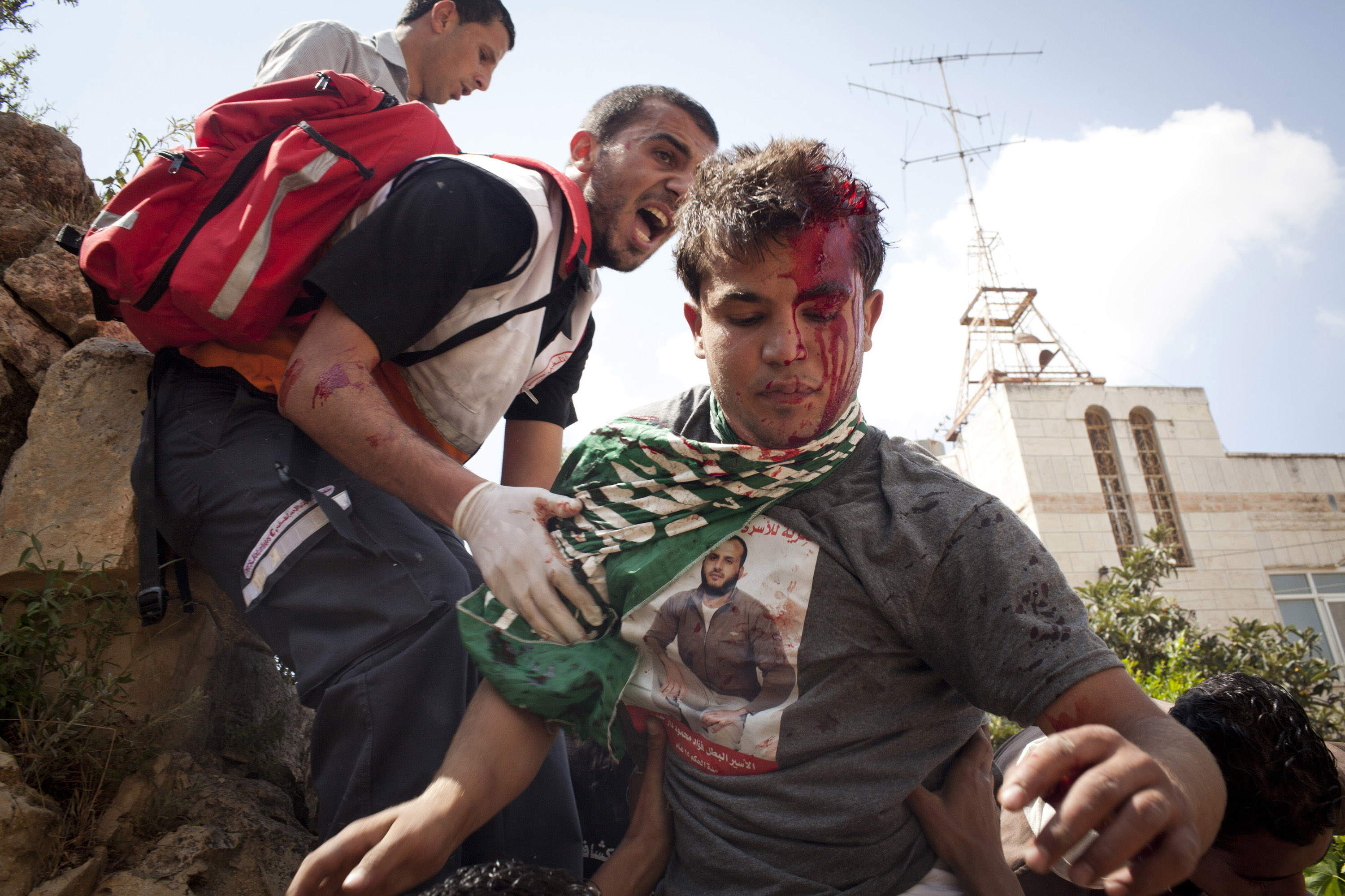 A Palestinian youth bleeds after he was beaten by several Israeli soldiers, injuring him in the head, during clashes following a protest commemorating the Nakba, outside Ofer military prison, near the West Bank city of Ramallah, May 15, 2012. (Photo by Oren Ziv/GroundTruth)