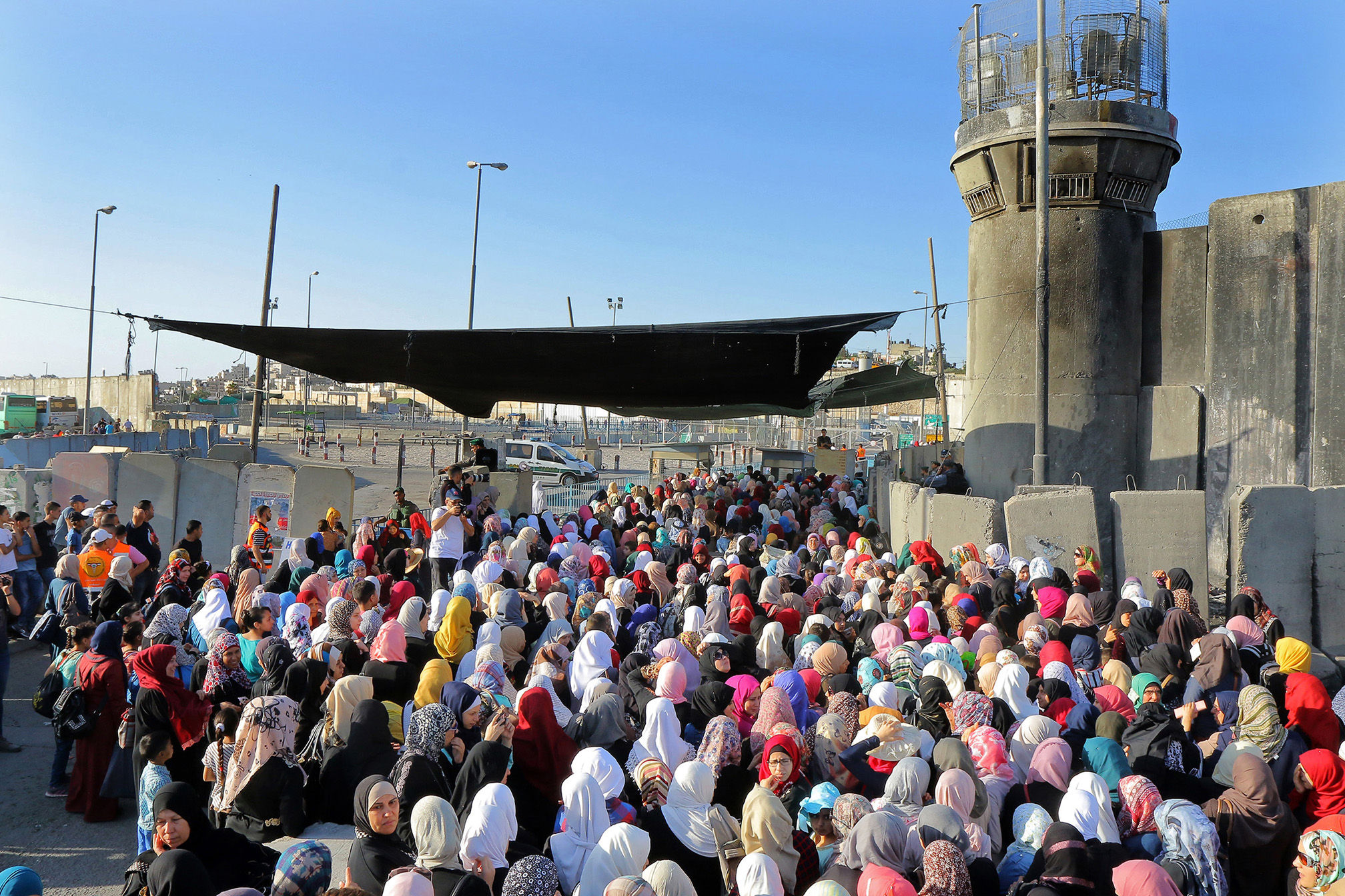 Palestinian women crossed through the Israeli military checkpoint of Qalandiya, a main crossing point between Jerusalem and the West Bank city of Ramallah,  headed to Jerusalem's Al-Aqsa mosque for the third Friday prayer of the holy Muslim fasting month of Ramadan, June 24, 2016.    (Photo by Ahmad Al-Bazz/GroundTruth)