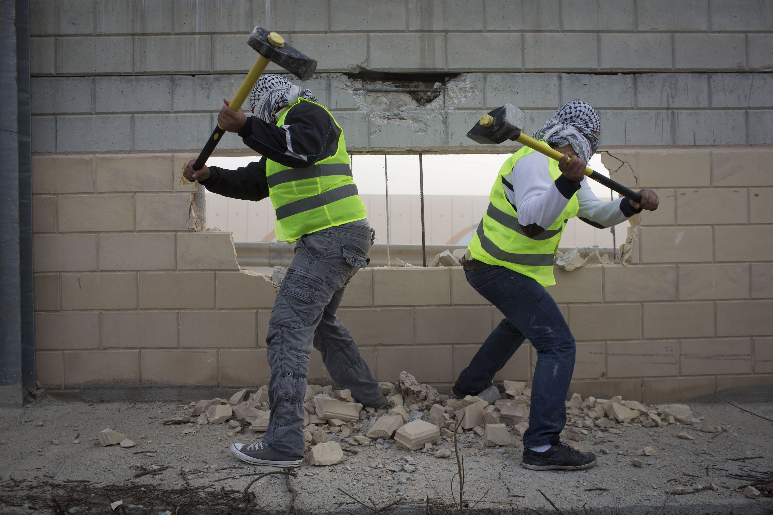 Palestinian activists destroyed part of the Separation Wall in the West Bank village of Bir Nabala, near Ramallah, November 15, 2013. (Photo by Oren Ziv/GroundTruth)