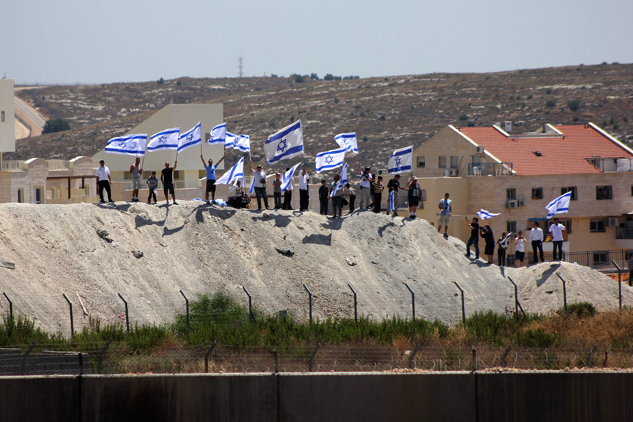 Israeli settlers from the illegal settlement of Modi'in Illit held Israeli flags and chanted slogans against Palestinian demonstrators on the other side of the Wall, during a weekly demonstration against the Israeli occupation and the Separation Wall in the West Bank village of Bil'in, June 28, 2013. (Photo by Ahmad Al-Bazz/GroundTruth)