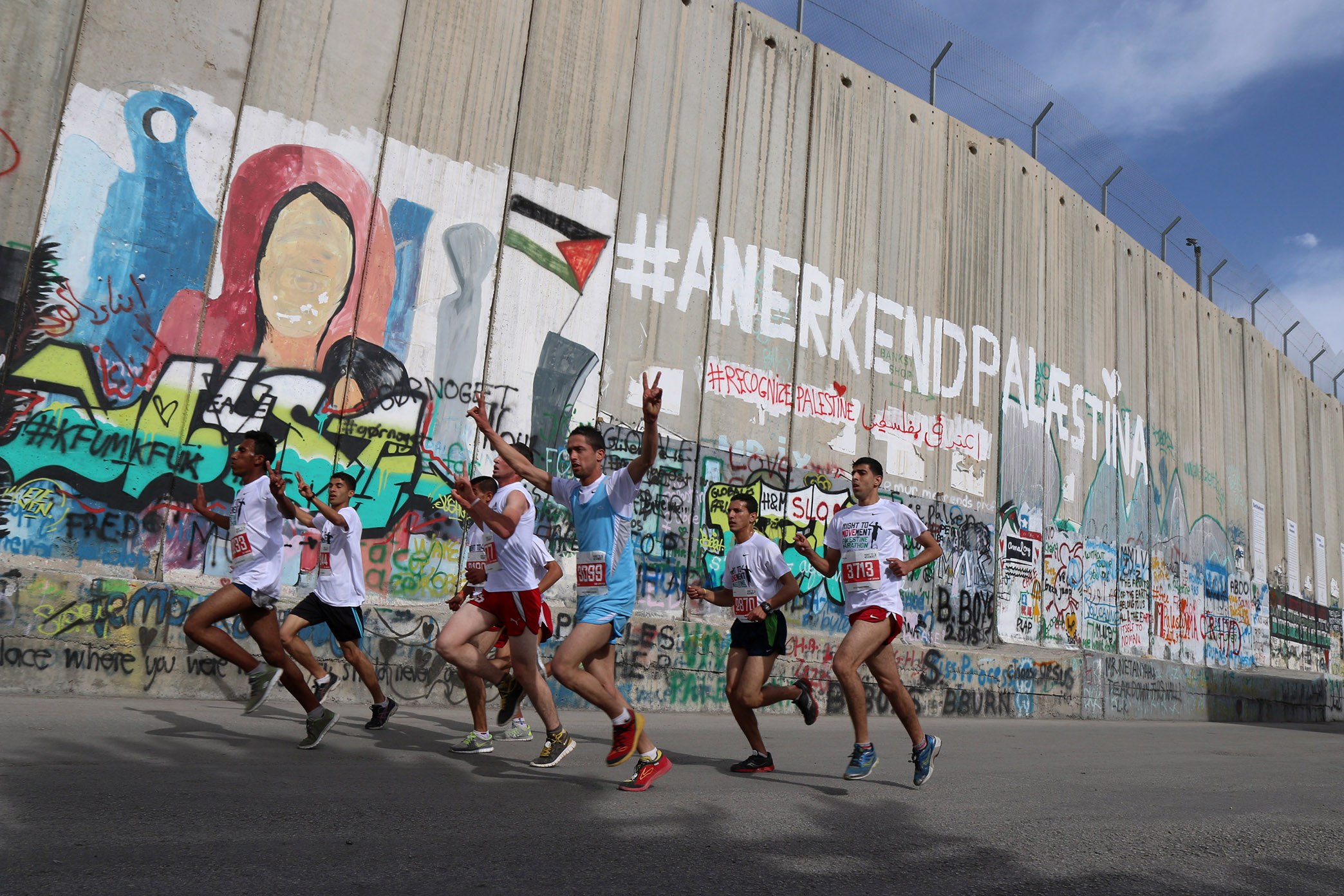 Some 3,200 runners raced along the Israeli Separation Wall dividing the West Bank city of Bethlehem during the third annual Palestine Marathon, March 27, 2015. (Photo by Ahmad Al-Bazz/GroundTruth)