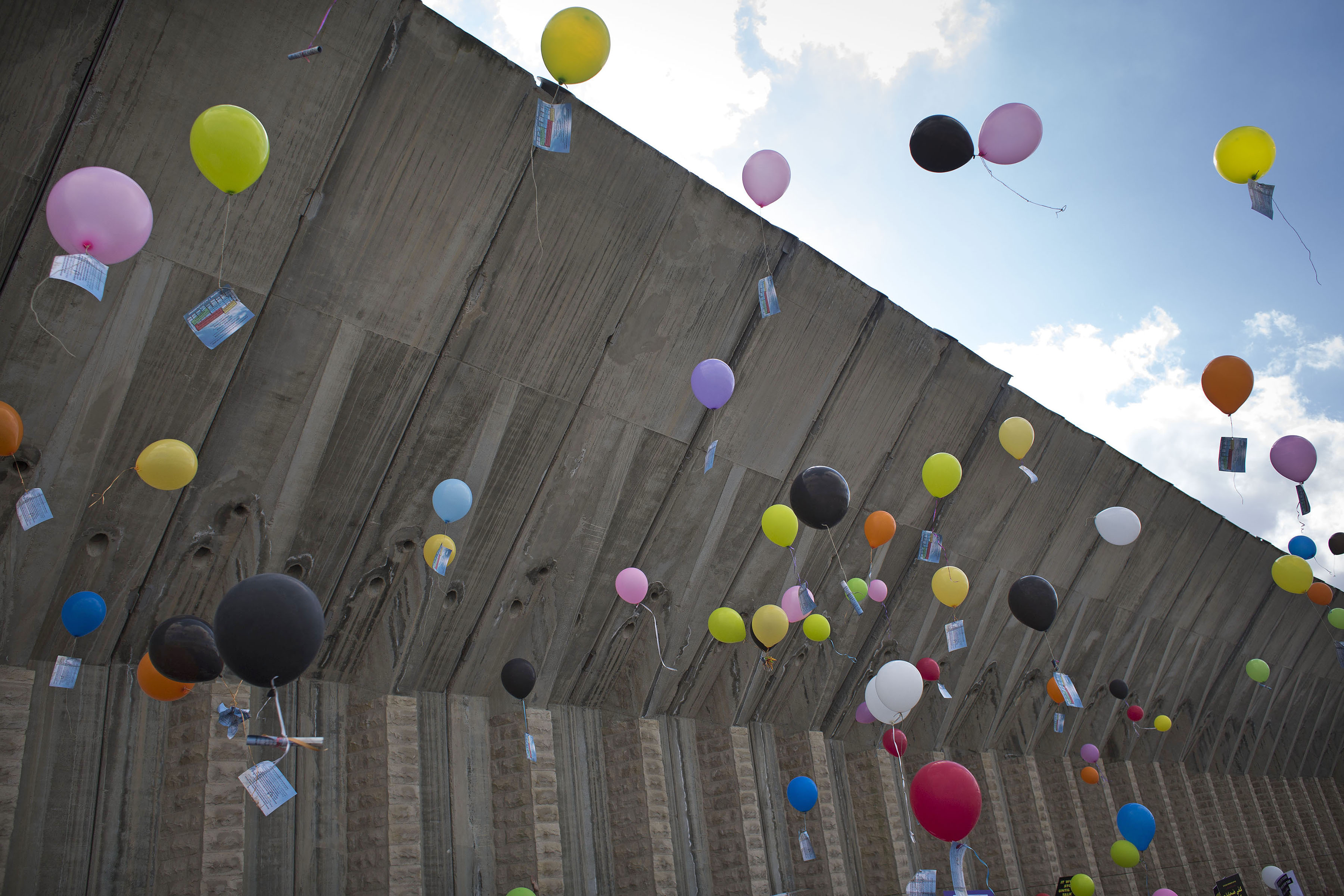 Israelis and Palestinians activists let go balloons along the Israeli separation wall during a march along the major Hebron-Jerusalem highway 60 in the southern West Bank to mark the international women's day and demanding an end to the occupation, Beit Jala, West Bank, March 4, 2016. (Photo by Oren Ziv/GroundTruth)