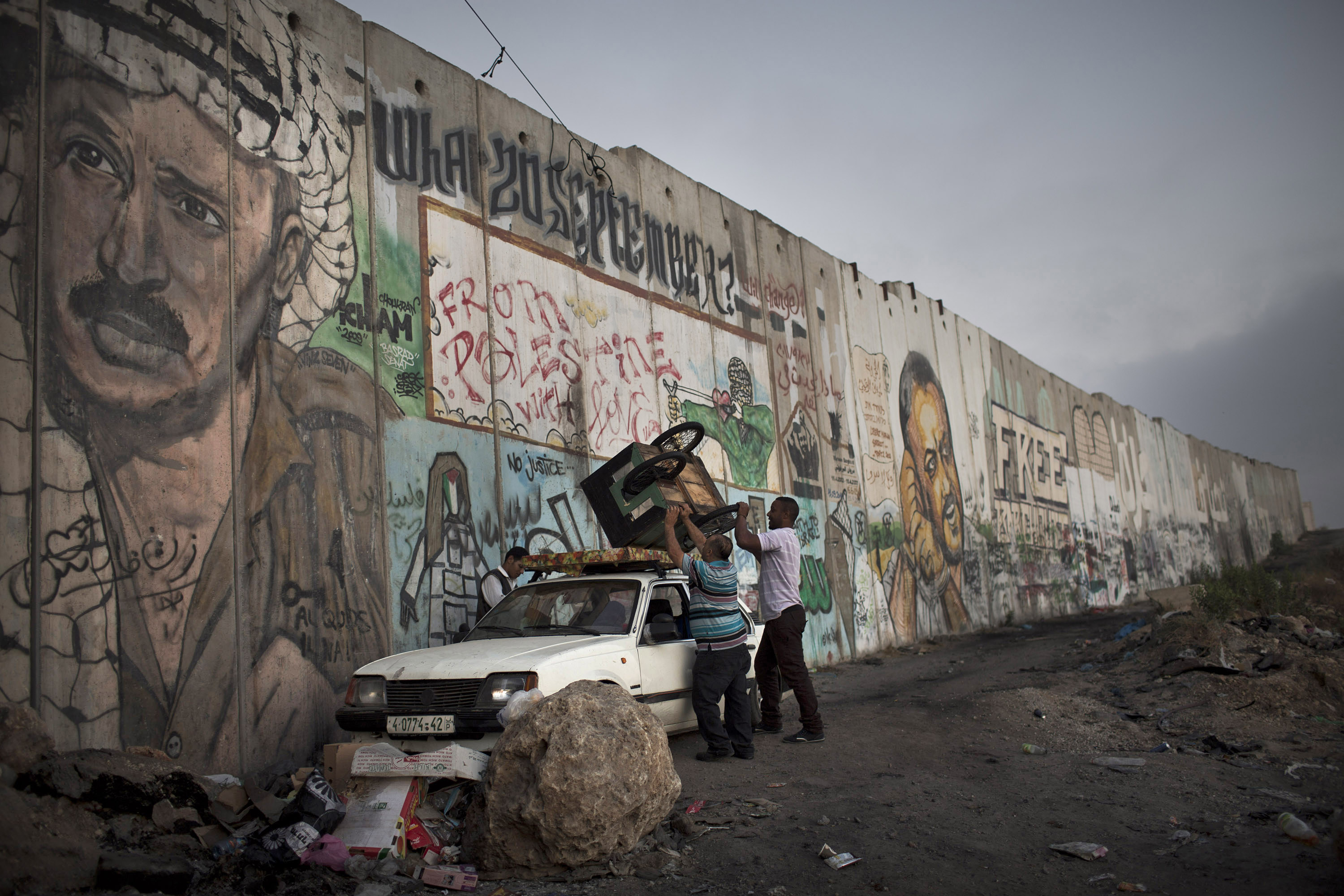 The Palestinian side of the wall is often painted with graffiti and political murals. These Palestinians loaded a cart on the third Friday of Ramadan, at the Qalandiya Checkpoint, West Bank, July 26, 2013. (Photo by Oren Ziv/GroundTruth)