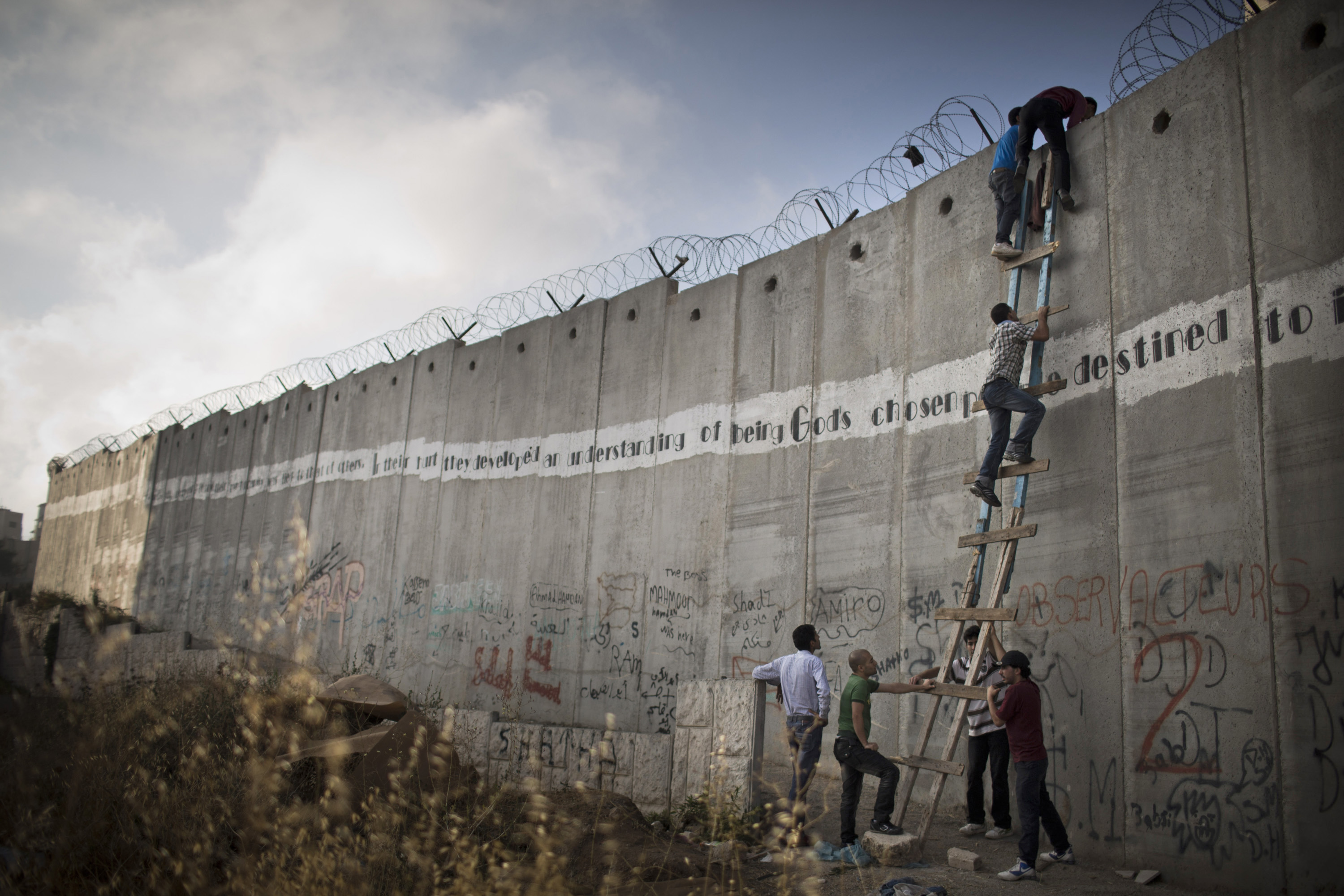 Palestinians used a ladder to climb over the Israeli wall in A-Ram, north of Jerusalem, on their way to the second Friday prayer of Ramadan near the Al-Aqsa mosque in the Old City, July 19, 2013. (Photo by Oren Ziv/GroundTruth)