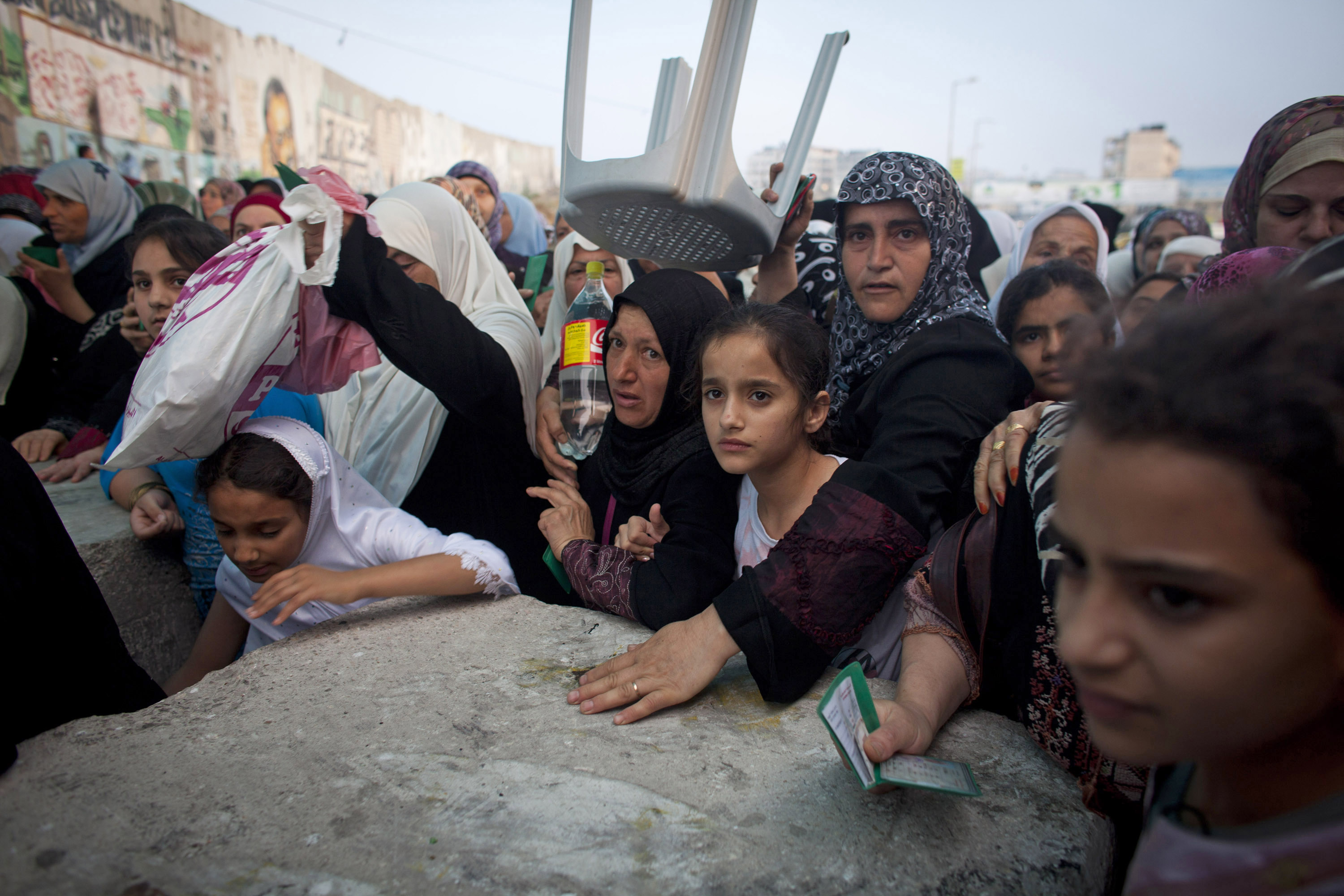 In the very early morning, Palestinian worshippers waited to cross into Jerusalem through the Qalandiya checkpoint in order to attend Friday prayers during Ramadan at the Al Aqsa Mosque, West Bank, July 27, 2012. During this time of increased traffic, women were separated from men and were forced to cross by the thousands through narrow cracks between cement blocks under the watchful eyes of Israeli soldiers and border police. (Photo by Oren Ziv/GroundTruth)