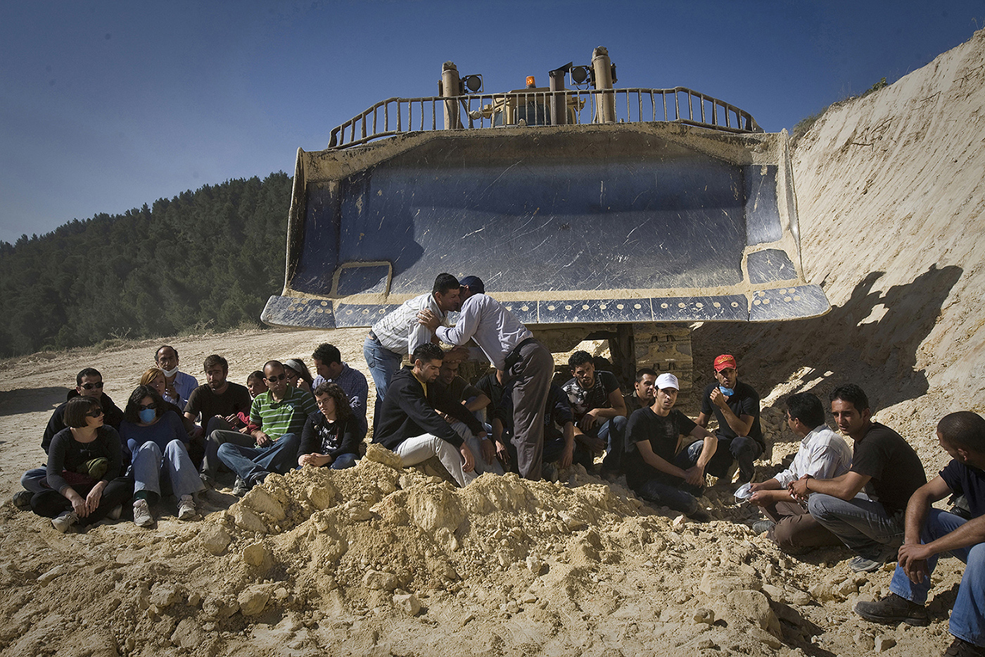 Palestinian villagers and supporting activists blocked the path of a bulldozer during a direct action against the building of the Separation Wall in Al-Walaja, West Bank near Bethlehem, May 6th, 2010. Most of the activists were arrested during the action. (Photo by Oren Ziv/GroundTruth)