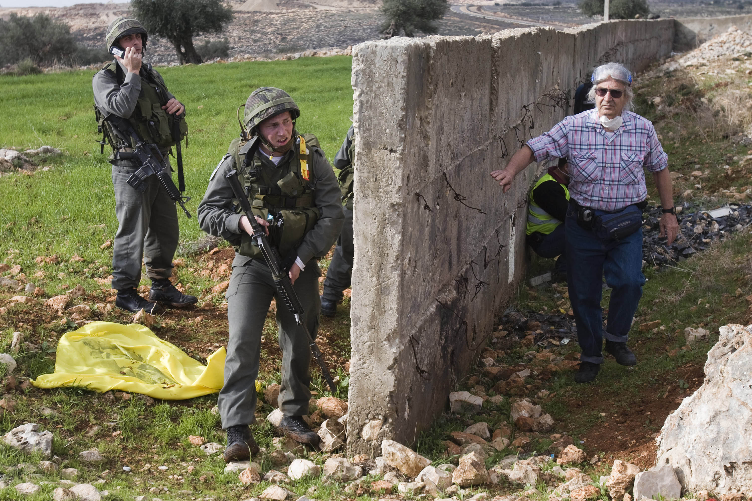 Armed soldiers and a veteran activist intersected during weekly protest against the Wall, Bil'in, West Bank, December 21, 2007
