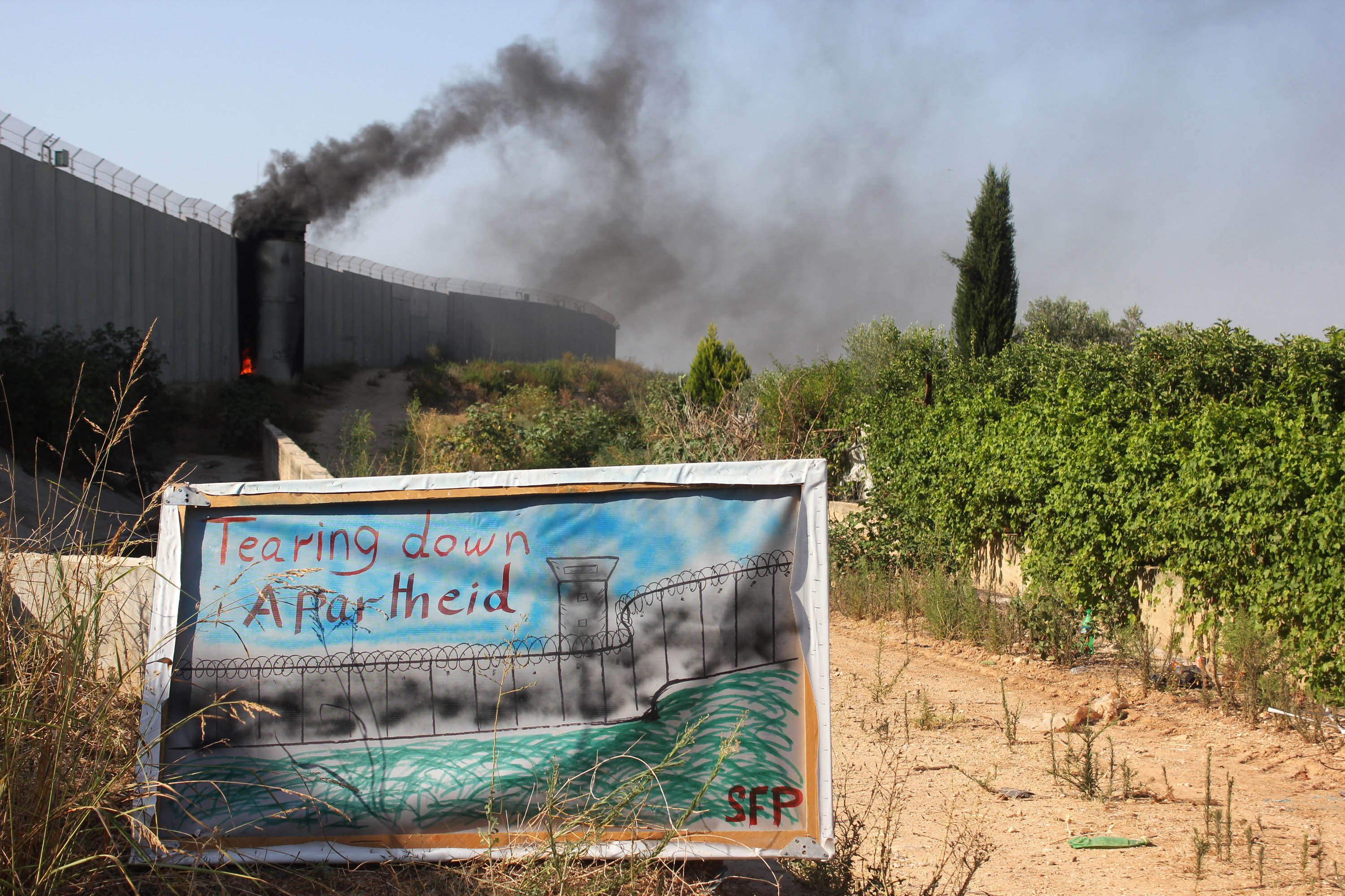 Palestinian and international activists burned a tower of the separation wall during an action on the 10th anniversary of International Court of Justice advisory opinion against the wall, Qalqilya, West Bank, July 9, 2014. (Photo by Ahmad Al-Bazz/GroundTruth)