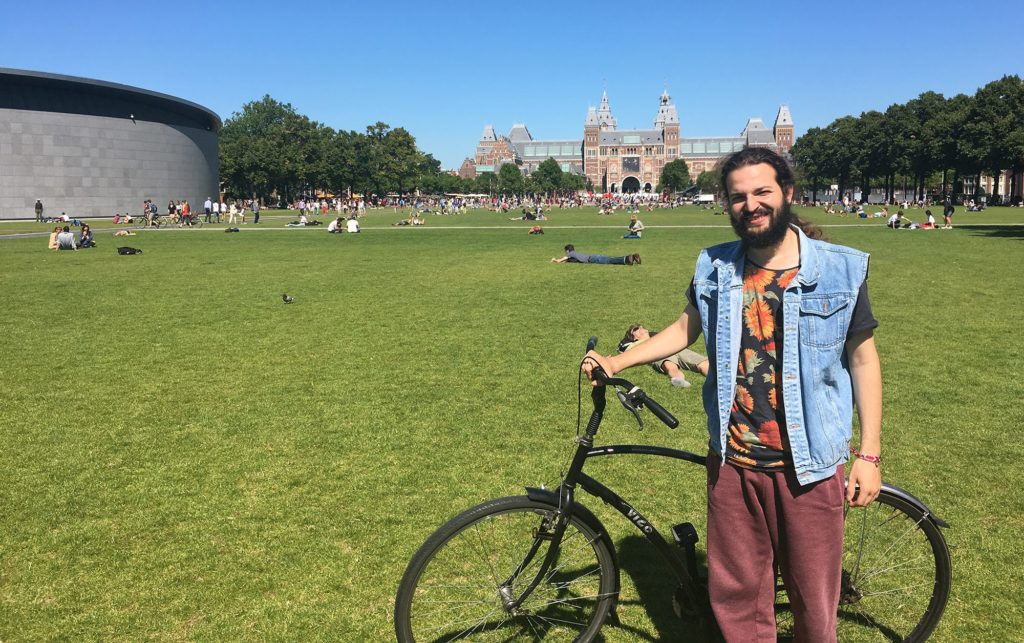 Ahmad Naffory poses with his bicycle in front of the Rijksmuseum in Amsterdam. He fled his native Syria four years earlier after the secret police came to his family's home. He settled as a refugee in Lebanon and pursued music. But after traveling to a music festival, he was denied re-entry into Lebanon and sought asylum in the Netherlands. (Jahd Khalil/GroundTruth)