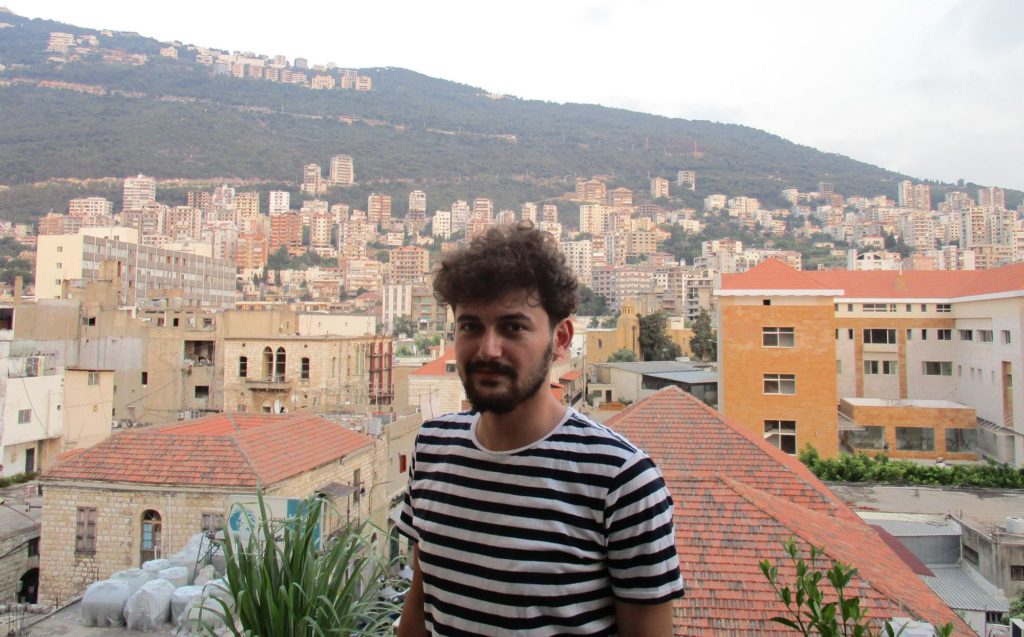 Assa'aleek's Sam Abdullah at sunset in his studio in Jounieh, north of Beirut. Jounieh is a resort town whose hotels have seen a boom in occupancy by Syrians. Sam's hotel is by the ocean, but his own room faces the mountains. He says the ocean creeps him out, after so many Syrians have died in the Mediterranean crossing to Europe. (Jahd Khalil/GroundTruth)