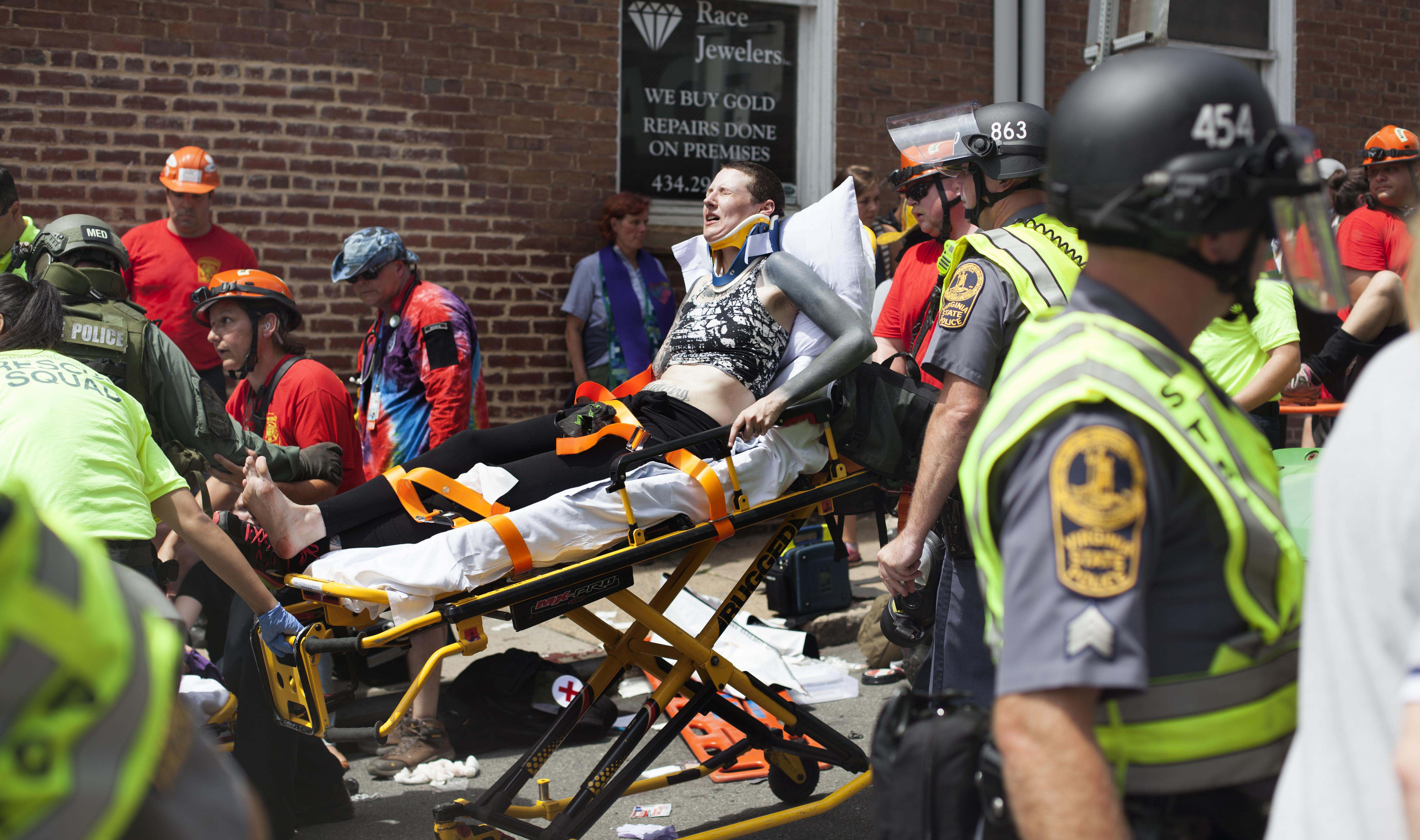 EMS and street medics treat counter protesters after a driver, later identified . by police as 20 year old James Alex Fields, Jr., plowed his car into the group. 32 year old Heather Heyer died, and 19 others were wounded in the attack. August 12, 2017, Charlottesville, VA. (Shay Horse/GroundTruth)