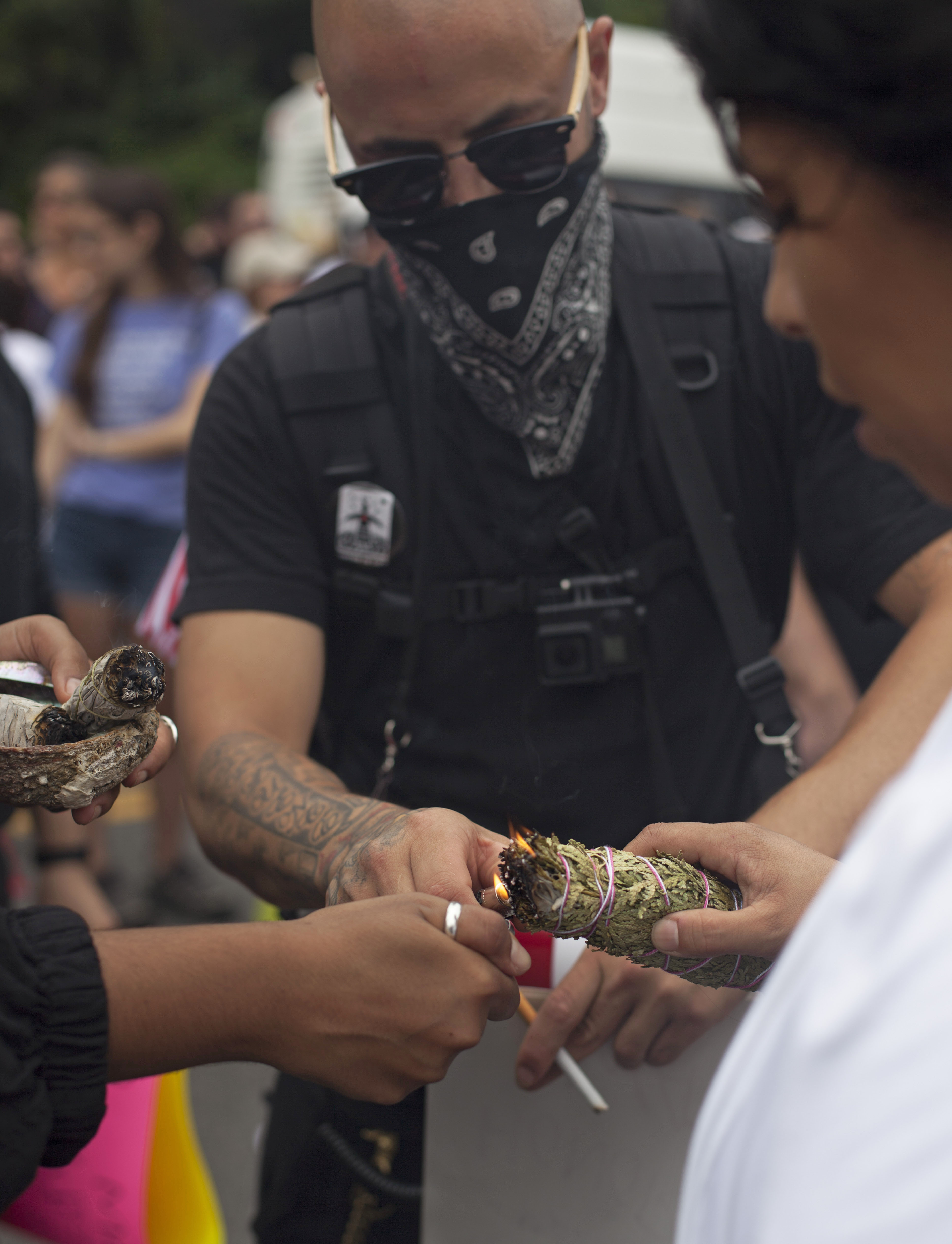 Counter protesters burn sage while amassing at the Reggie Track & Field Center in Roxbury. The counter demonstration was against the Free Speech rally at the Boston Common. (Shay Horse/GroundTruth)