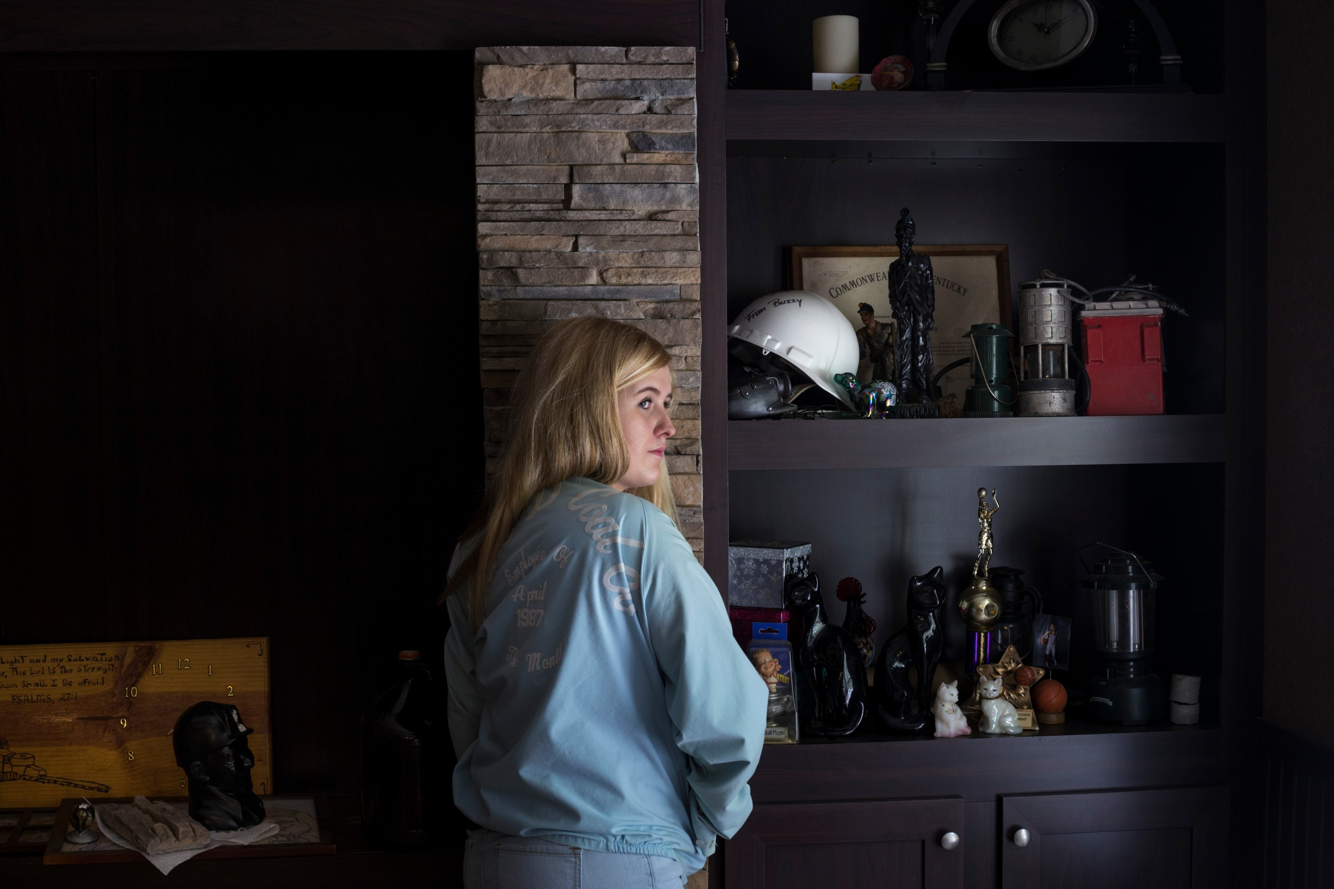 Lizzie Jones, 17, proudly wears her father's employee of the month jacket from his time working at the coal mines nearby a shelf of her family's relics of the coal industry at her home in Eastern Ky., on Sunday, September 24, 2017. Jones' father passed away from black lung in 2014. In January of 2017 her mother, who also worked in the coal mining industry, passed away. Jones said she has plans on moving into the home they once shared and has developed a complex relationship with the coal. (Photo by Brittany Greeson/GroundTruth)