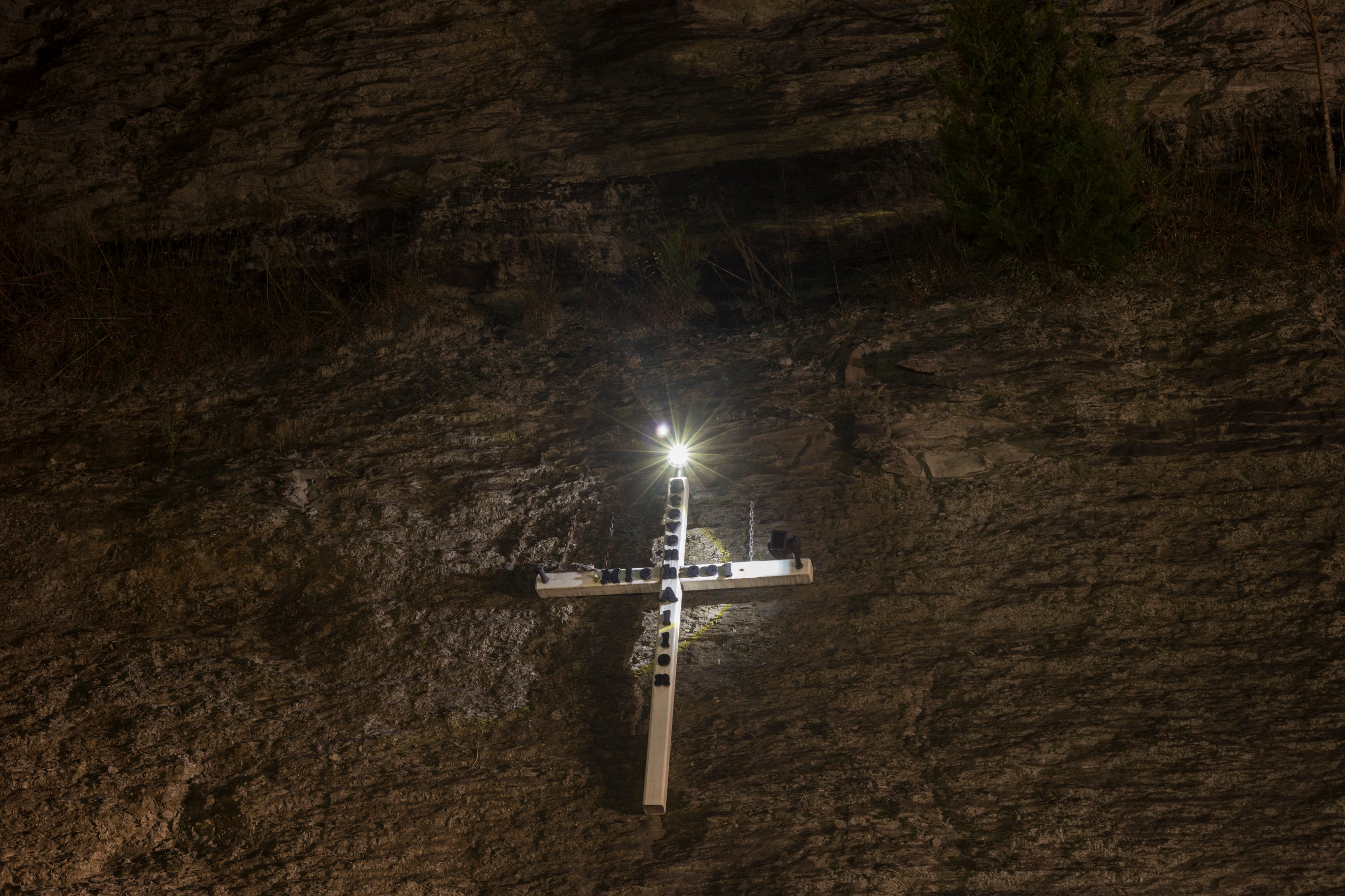 A cross in honor of a man named Steven Michael Allen is nailed into a wall of rock along I-23 near Tram, Ky., on Sunday, September 23, 2017. (Photo by Brittany Greeson/GroundTruth)