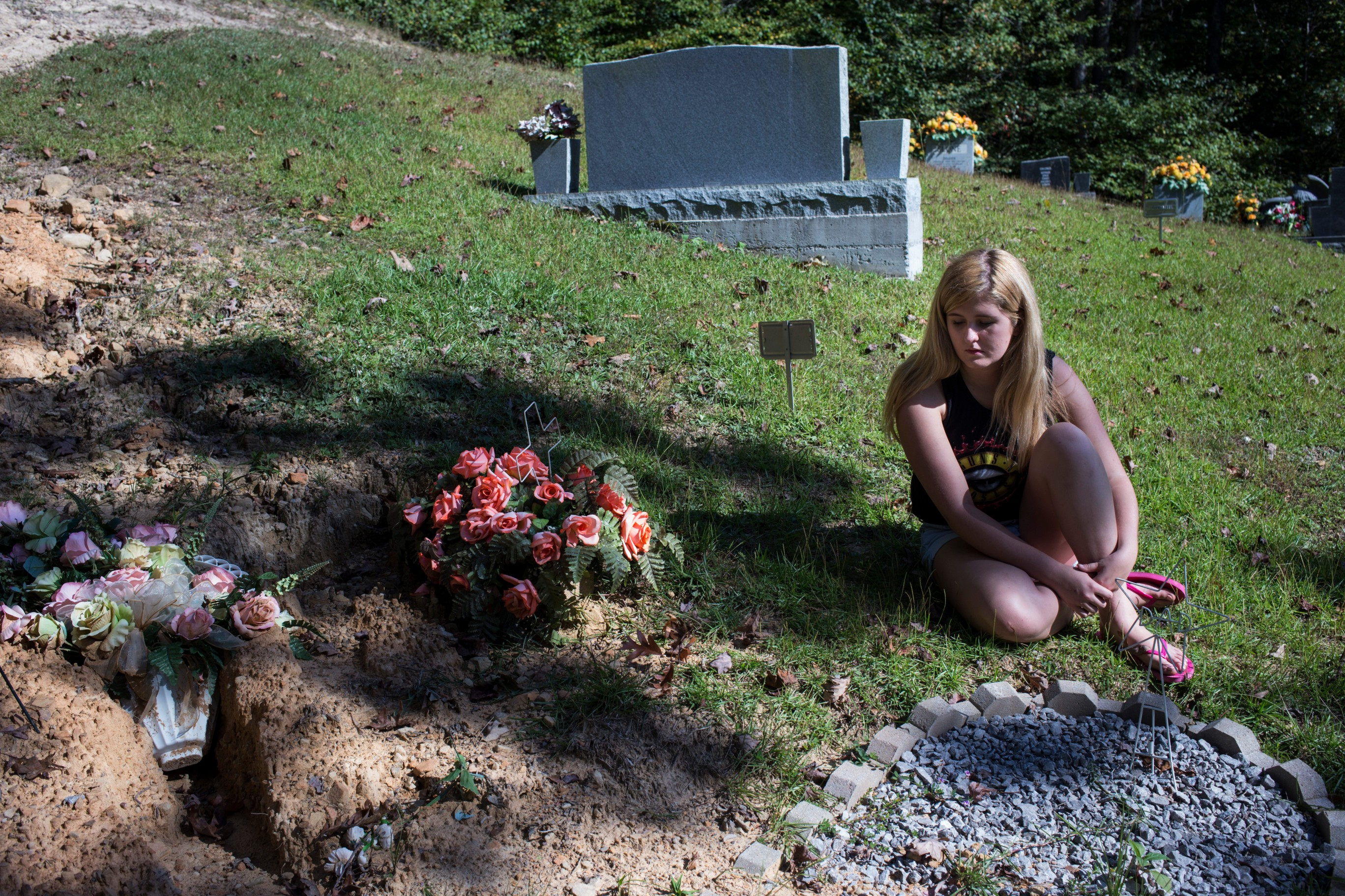 Lizzie Jones visits the grave of her parents in Belvinsville Ky., on Sunday, September 24, 2017. Jones said she likes to sit in silence when she visits with her parents as she feels like she's having an internal dialogue with them that is more spiritual than it is direct. (Photo by Brittany Greeson/GroundTruth)