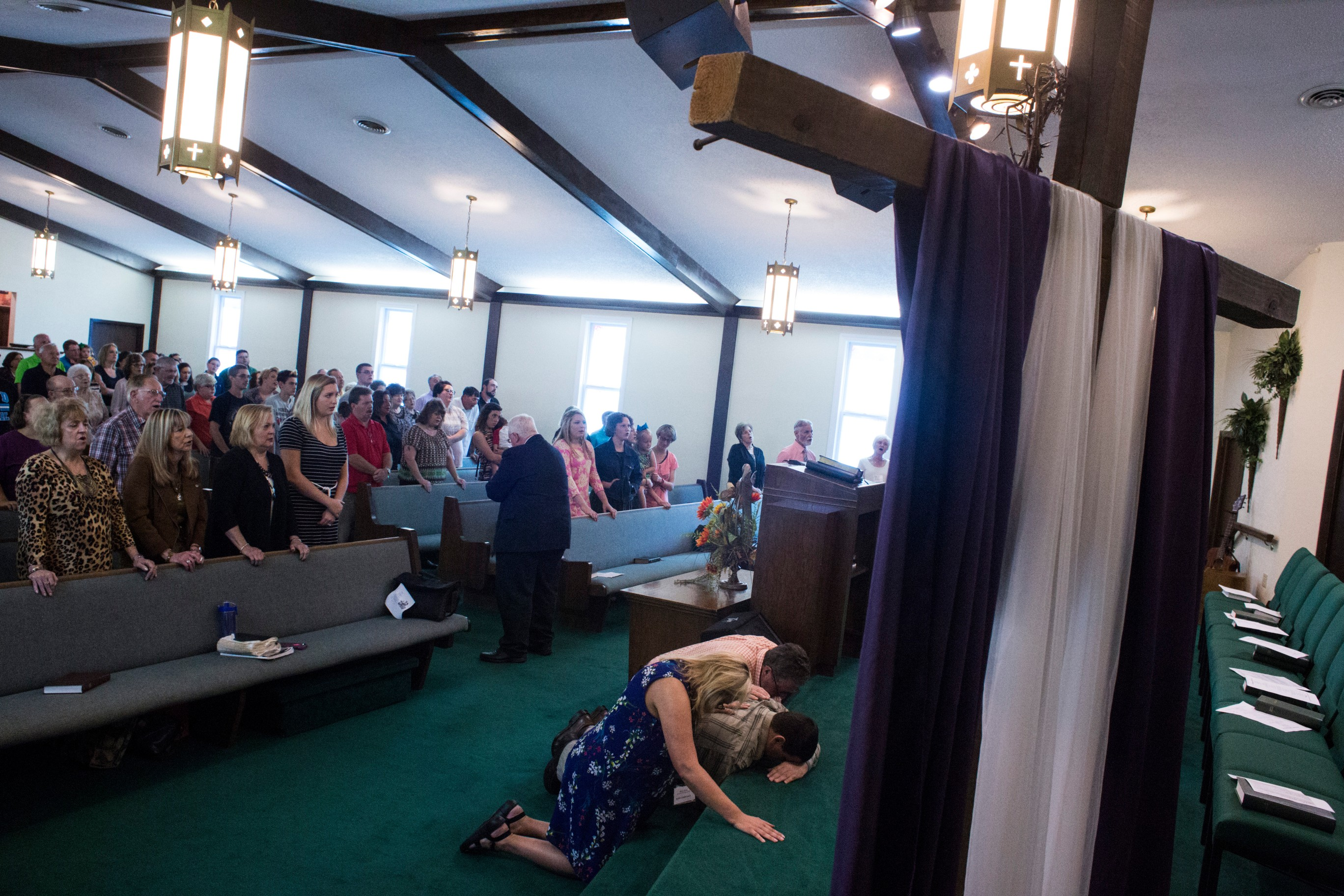 Mary Sloane, an English teacher at Floyd Central High School, prays for a member of her congregation at First Baptist Church in McDowell, Ky., on Sunday, September 24, 2017. (Photo by Brittany Greeson/GroundTruth)