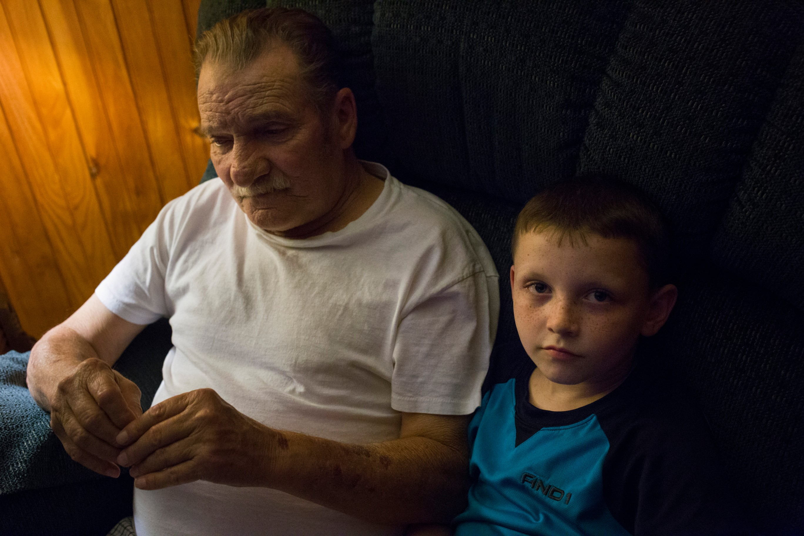 Chase Newman, 8, sits in a reclining chair with his grandfather Doff Justice as he watches TV at their home in Grethel Ky., on Thursday, September 28, 2017. (Photo by Brittany Greeson/GroundTruth)