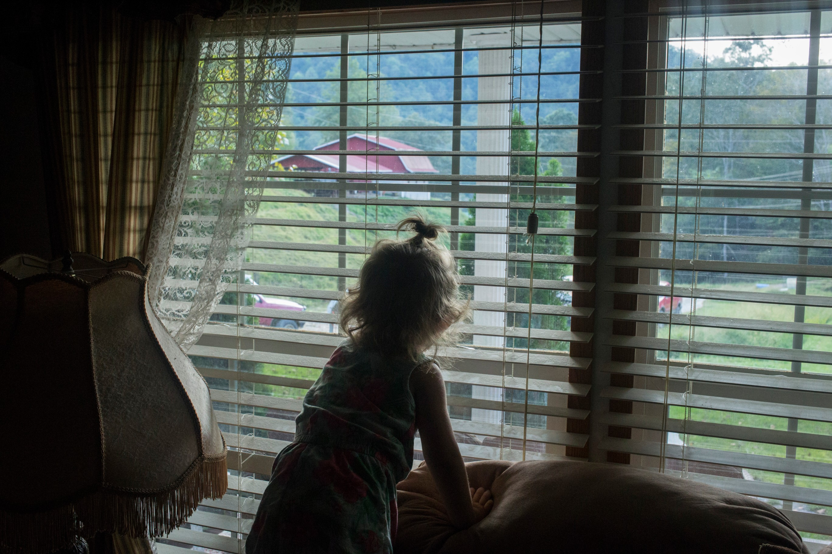Paisley Jarvis, 2, peeks out the window of her father's living room in Langley, Ky., on Tuesday, September 26, 2017. (Photo by Brittany Greeson/GroundTruth)